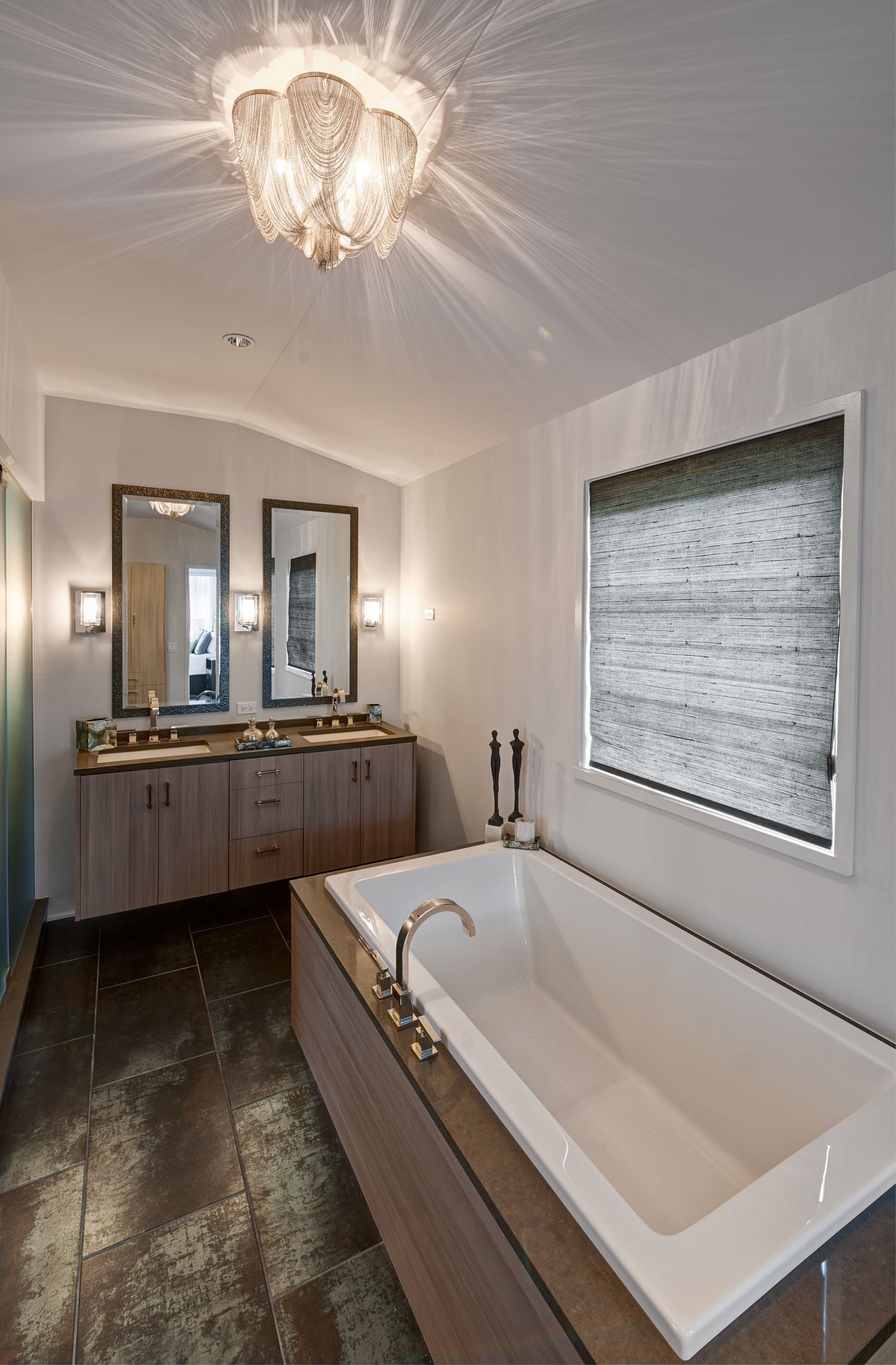 Fort Sheridan Ranch - Master Bathroom   Italian porcelain flooring in large 12 x 24staggeredpattern. Vanity and tubsurrounded in a custom wood finish. Overheadchain light fixture and three sconcesprovide beautiful lighting.
