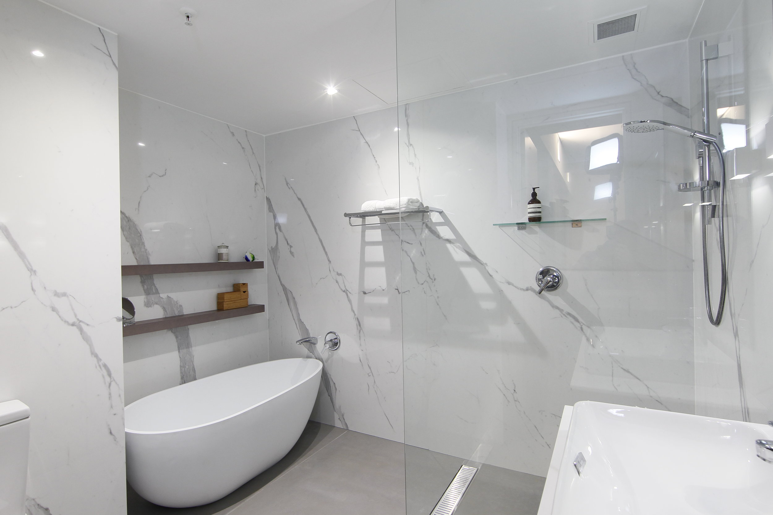 For the clean freak…this White Marble look wall tile offers minimal grout lines in this stunning bathroom.