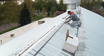 Installing the ridge cap on this new metal roof replacement project.