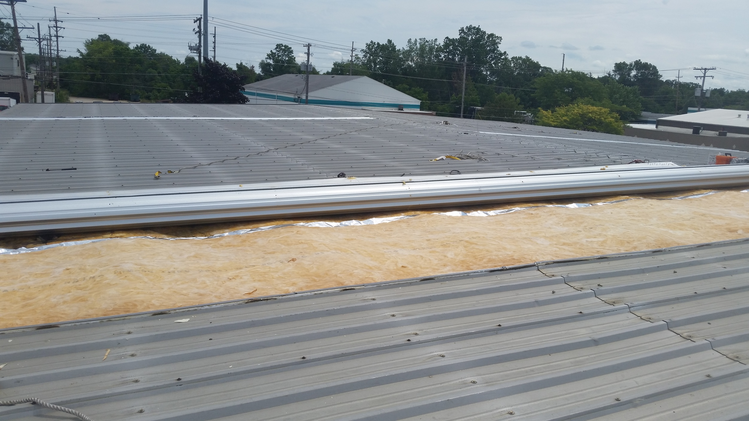 Metal building insulation replacement, view from the roof. New insulation has been installed. Lapel MI, August 2016