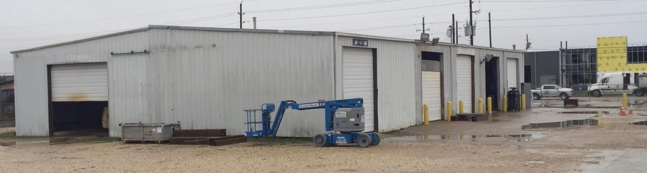 Before metal building repairs , rear view of pre-engineered metal building. Damaged metal wall panel need repairs.