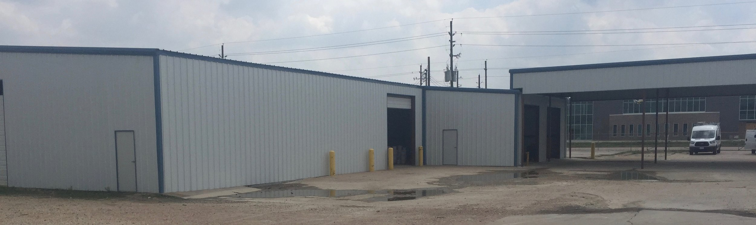 After a metal building wall and roof renovation - removed three overhead doors, re-located two overhead doors. Rear view. Small addition at front right.