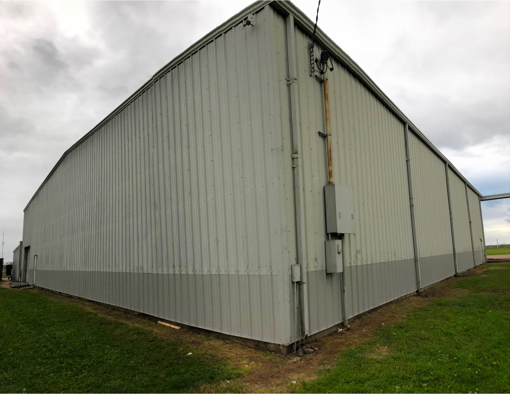The bottom of the metal building wall panel was rusted out and pushed out in places on this airport hangar. The bottom 4' of metal wall panel, base angle and insulation were replaced. The panels are the same color, the old top panels are just dirty. This was much affordable than replacing the entire panel.