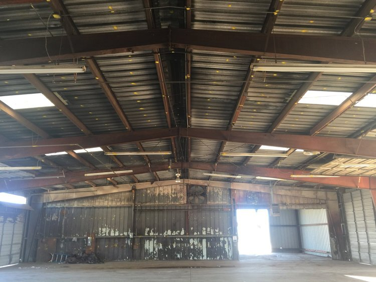 This abandoned building was very rusty. - We installed 3 new overhead doors, removed three overhead doors, installed two new man/pass doors, removed and replaced 15 purlins, and cleaned, primed and painted all of the steel.