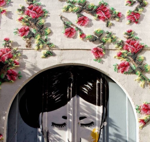 The Artist is  Raquel Rodrego . You can read more about her giant  delicate cross-stitch flowers all over Madrid here .