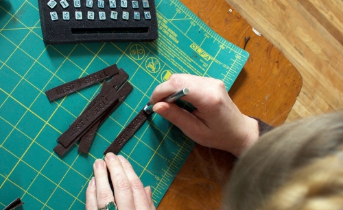 Hand stamping my name on repurposed leather.