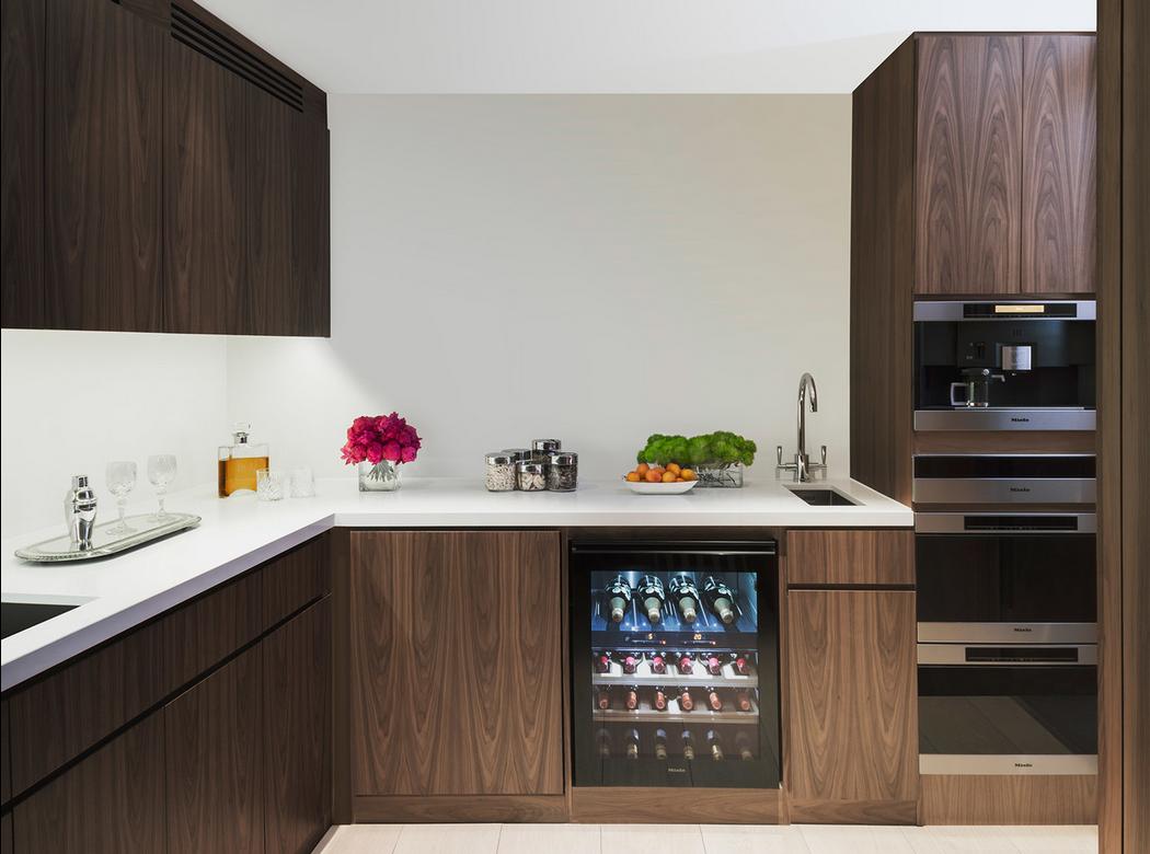 Dark wood in the kitchen, wine fridge, sleek white counters, Miele Appliances.