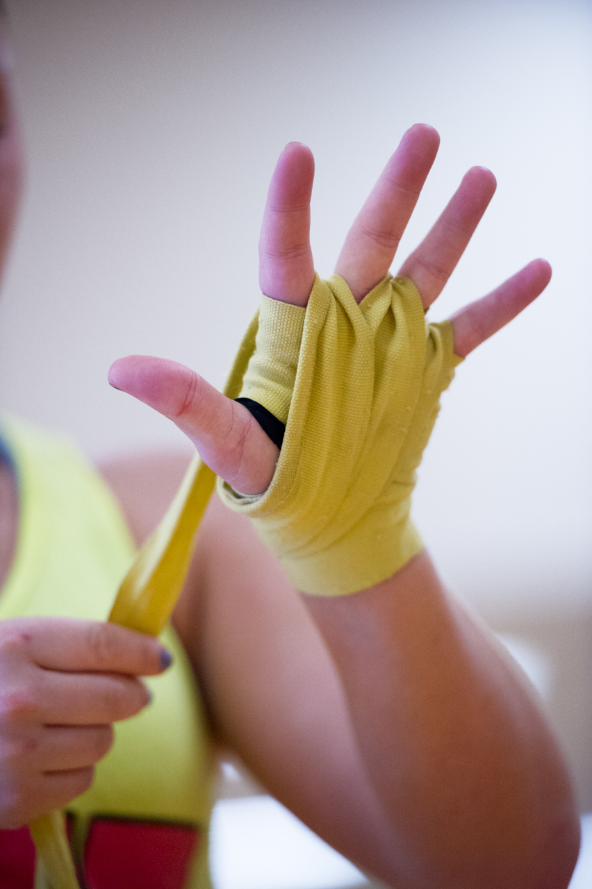 Sheeley applies hand wraps that she wears under her boxing gloves before her training session at the Ping Center on September 9, 2015, in Athens, Ohio. Hand wraps provide stability for the bones when boxing and prevent the skin from blistering. (©2015 Sarah Stier)