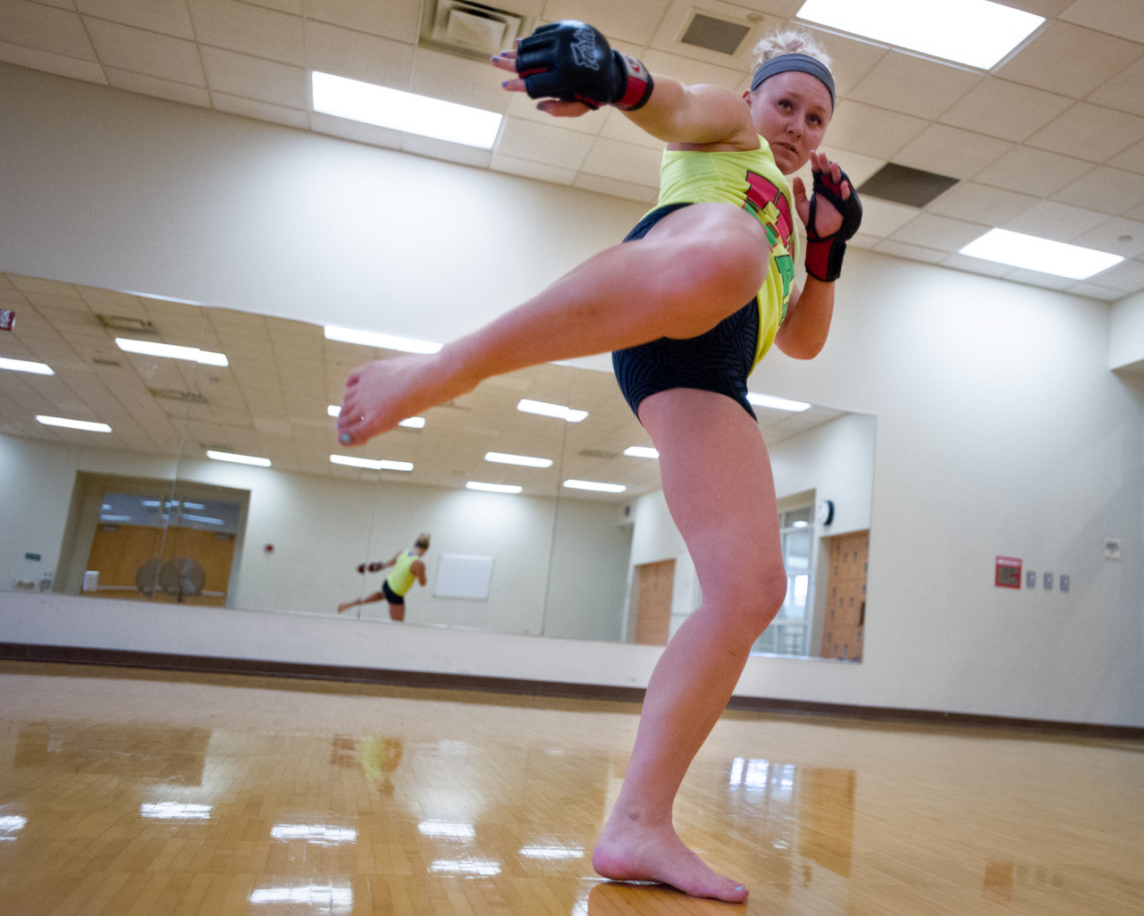 """Sheeley does a side kick while """"shadow boxing"""" during her training session at the Ping Center on September 9, 2015, in Athens, Ohio. """"The first time I got kicked in the face in practice, another female fighter kicked my nose and I got tears in my eyes but I got back up. After that I learned to start using the bruises as my trophies,"""" says Sheeley. (©2015 Sarah Stier)"""
