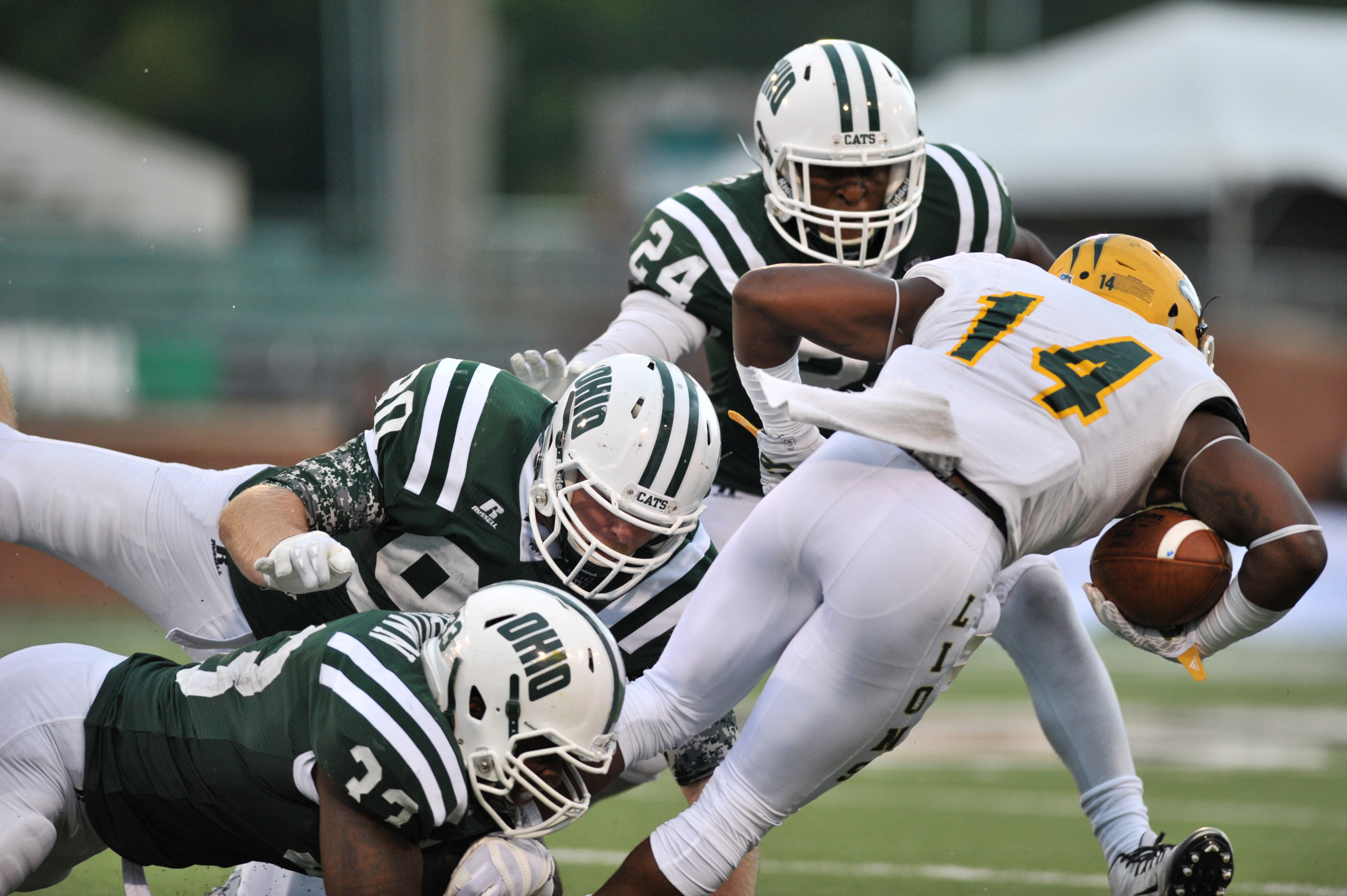 Ohio University football players Blair Brown (#33), Trent Smart (#90), and Toran Davis (#24) tackle Southeastern Louisiana wide receiver Jeff Smiley. The Bobcats won the game with a score of 35-14 on September 19, 2015, at Peden Stadium in Athens, Ohio.