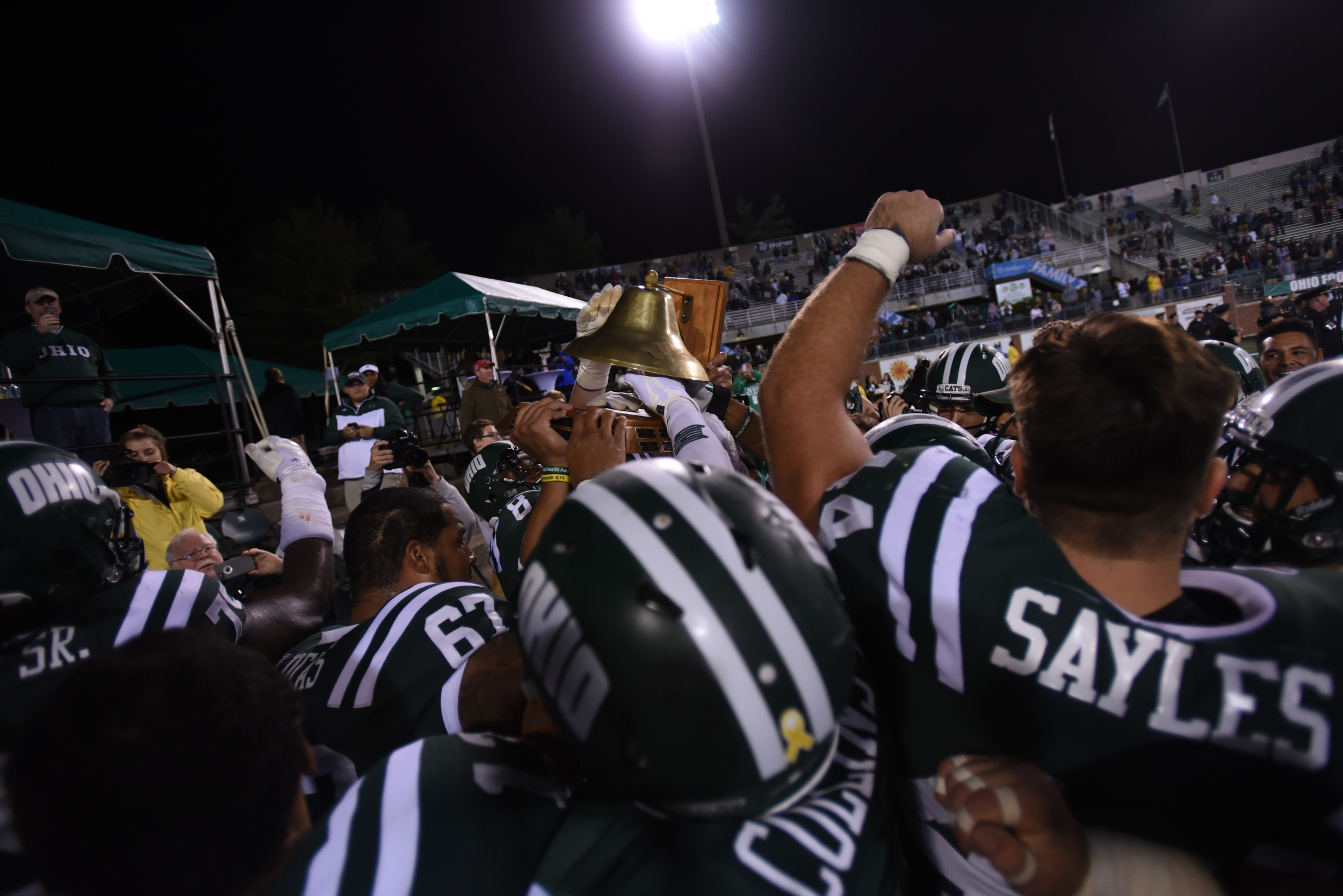 """Members of the Ohio Bobcats Football Team hoist the bell that they claimed after a 21-10 win over Marshall on September 12, 2015. The """"Battle for the Bell"""" game originated between the two schools in 1905. ©2015 Sarah Stier 