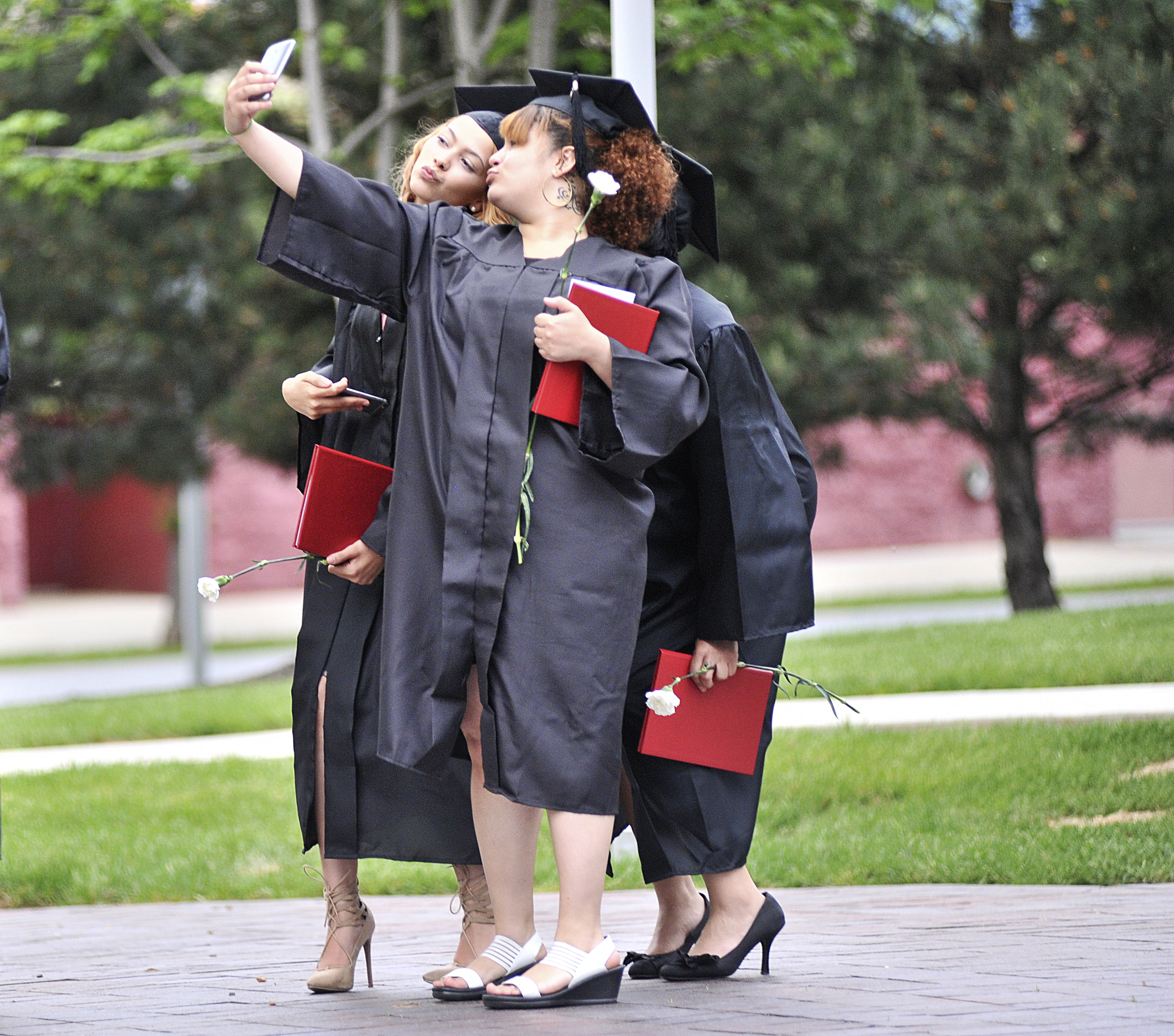 Demilee Alvarez, Imani Livingston, and Selenia Mendez take a photo together after Reading Area Community College's GED commencement ceremony on May 18, 2016, in Reading, Pennsylvania.