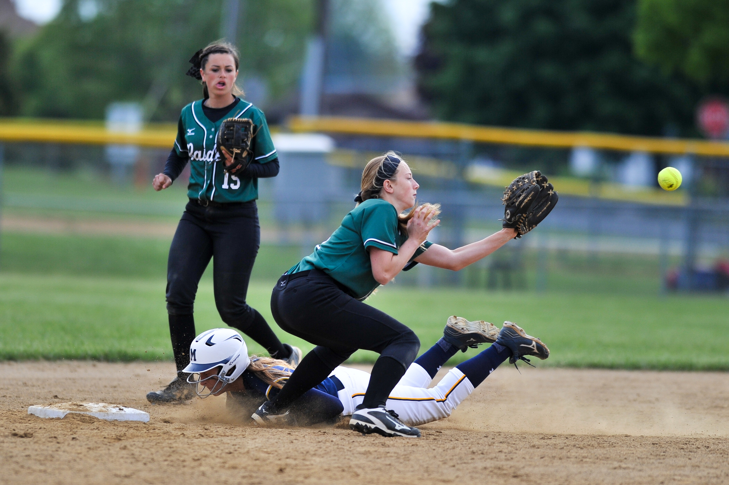 A softball play from Twin Valley High School attempts to catch the softball as her opponent from Muhlenberg High School slides into second base. The game was a semi-final on May 17, 2016,for the Berks County Championship tournament at Lyons Ballfield.