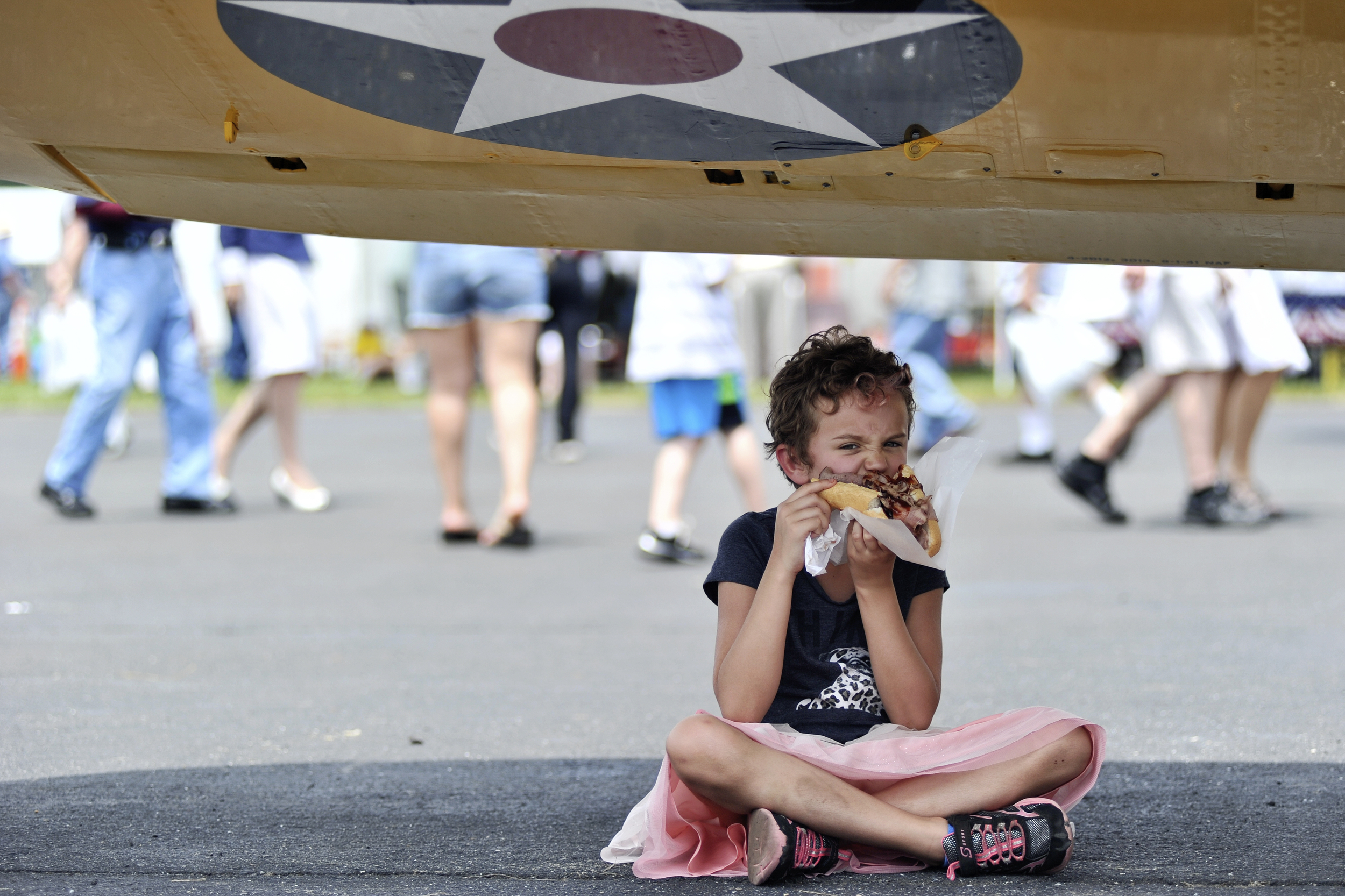 Addie Whitham, 8, of Philadelphia, PA, grabs a bite to eat under the shade of a plane wing at the World War II Weekend in Reading, PA, on June 4, 2016. (Reading Eagle: Sarah Stier)