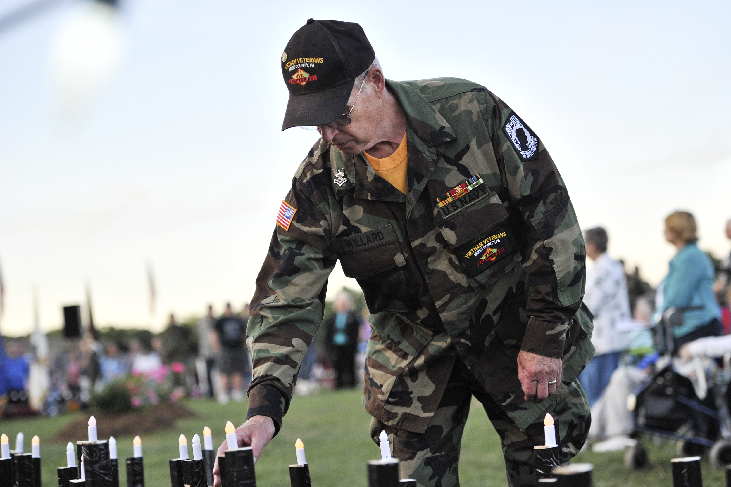 Joe Willard of Muhlenberg Township places a candle in memory of a fallen soldier at the candlelight ceremony on June 10, 2016, at the Moving Wall at Jim Dietrich Park in Muhlenberg Township, PA. (Sarah Stier: Reading Eagle)