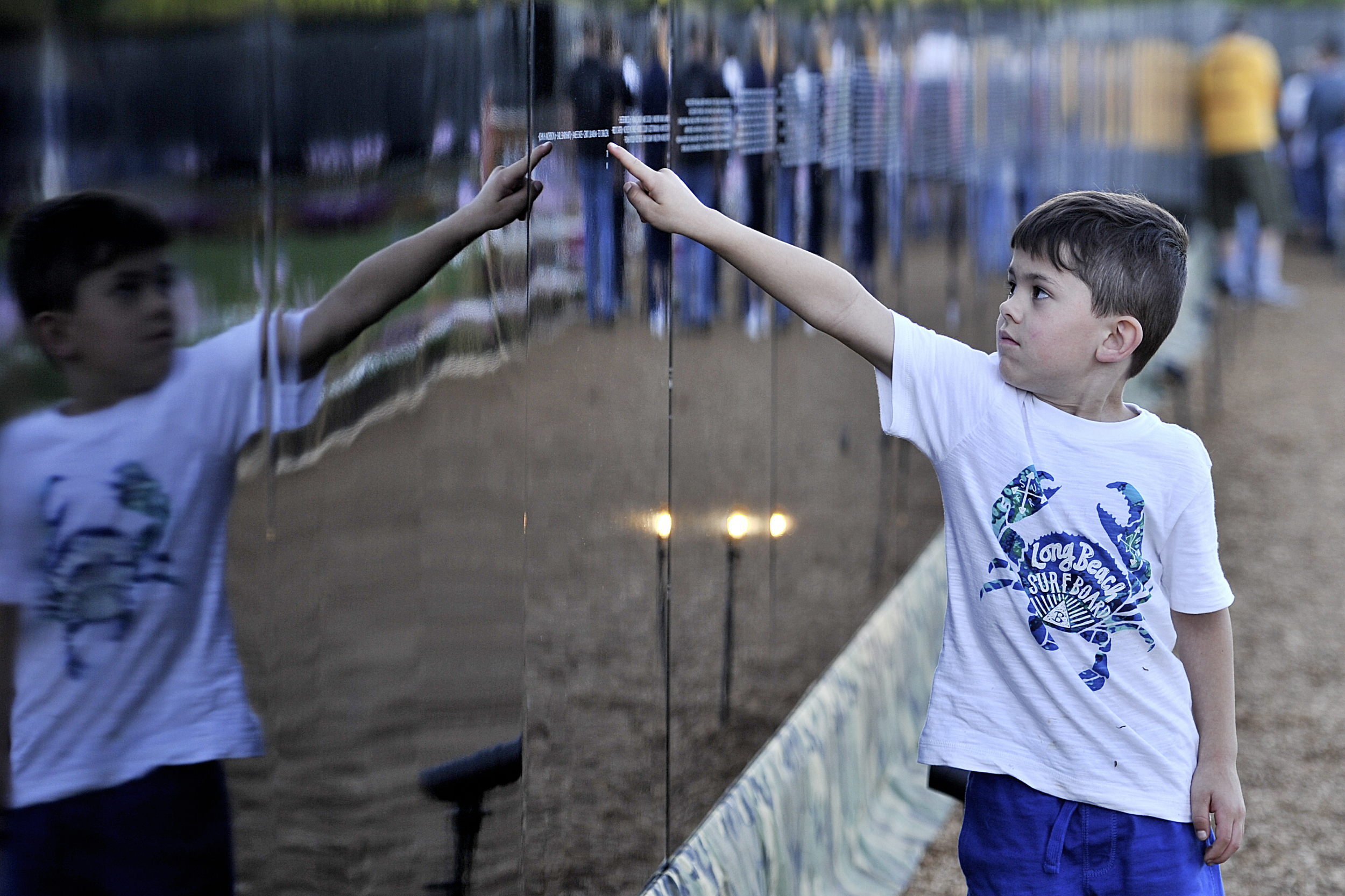 Gavin Jacobs, 6, of Leesport looks at the names on the wall at the Opening Ceremony for the Vietnam Memorial Moving Wall in Muhlenberg, PA, on June 9, 2016. (Sarah Stier: Reading Eagle)