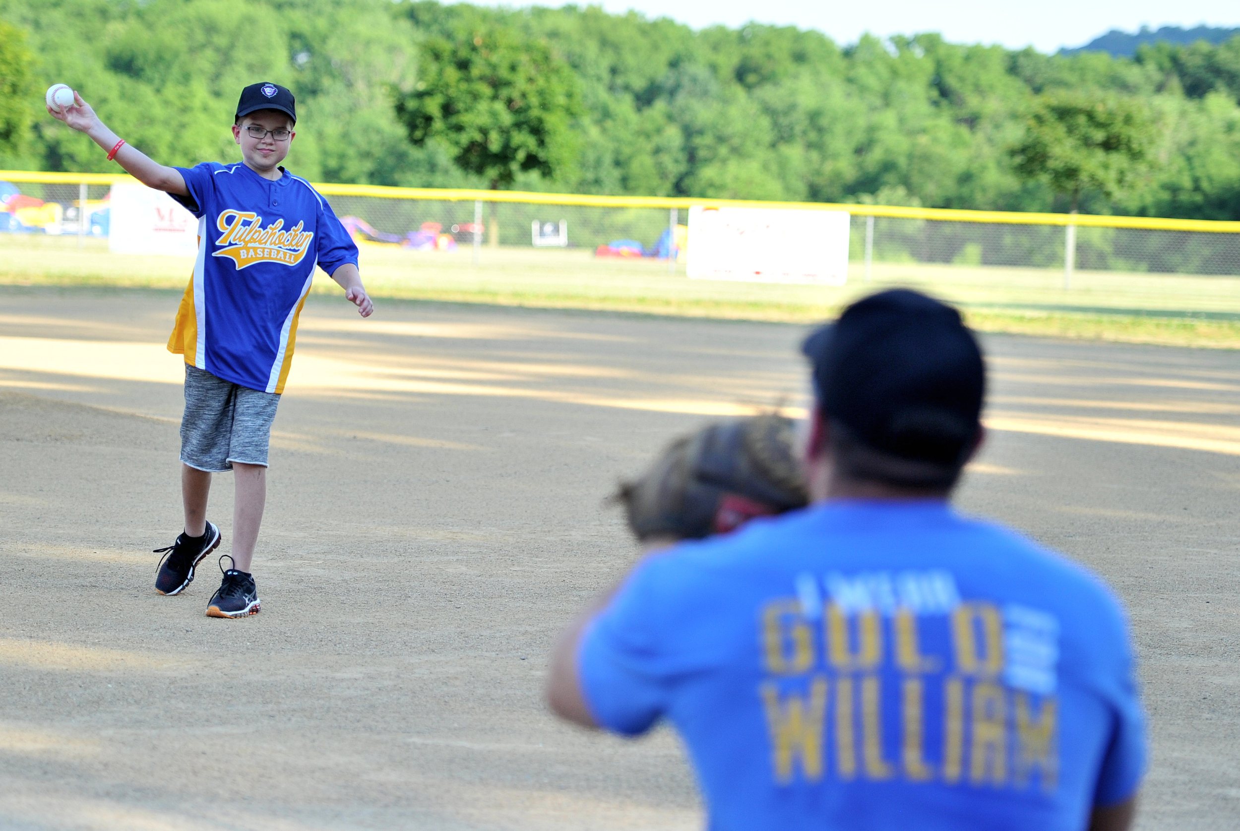 Caption/Description: William Dieffenbach, 11, of Womelsdorf throws the first pitch of the game to his father Nevin Dieffenbach at the Strike Out Cancer event in Bernville, PA, on June 19, 2016. William is battling brain cancer, and the event was held to raise money for cancer research. (Reading Eagle: Sarah Stier)