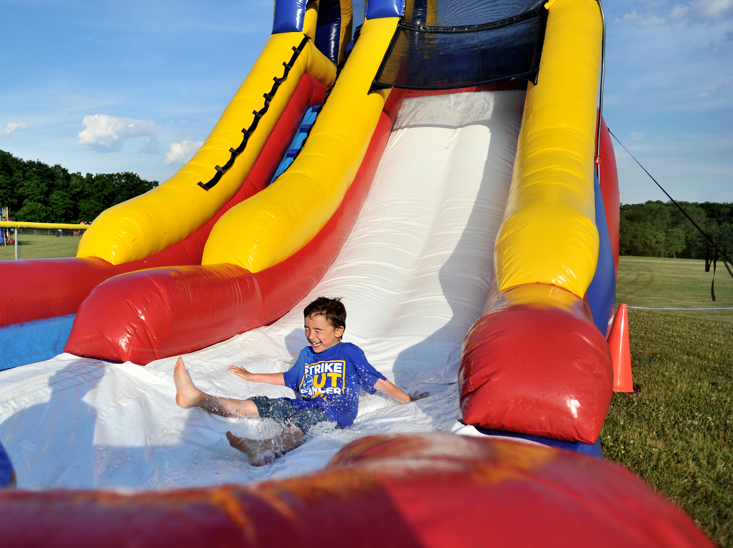 Kaydon Batz, 6, of Womelsdorf splashes into water at the bottom of an inflatable slide at the Strike Out Cancer event in Bernville, PA, on June 19, 2016. (Reading Eagle: Sarah Stier)