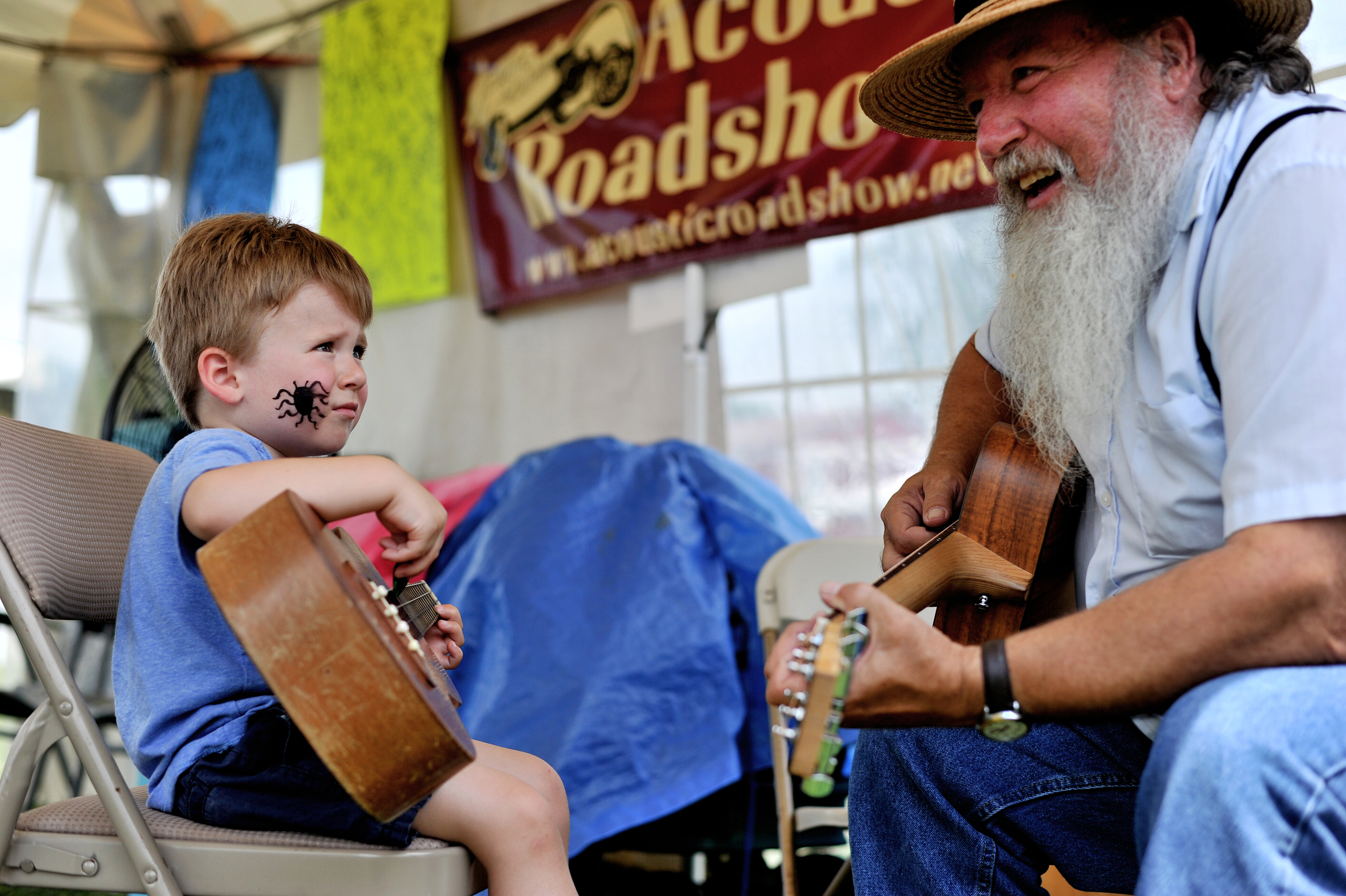 Lukas Cook, 2, of Branchburg, NJ, and Butch Imhoff of Hamburg play together at the Kutztown Folk Festival in Kutztown, PA, on July 5, 2016. (Reading Eagle: Sarah Stier)
