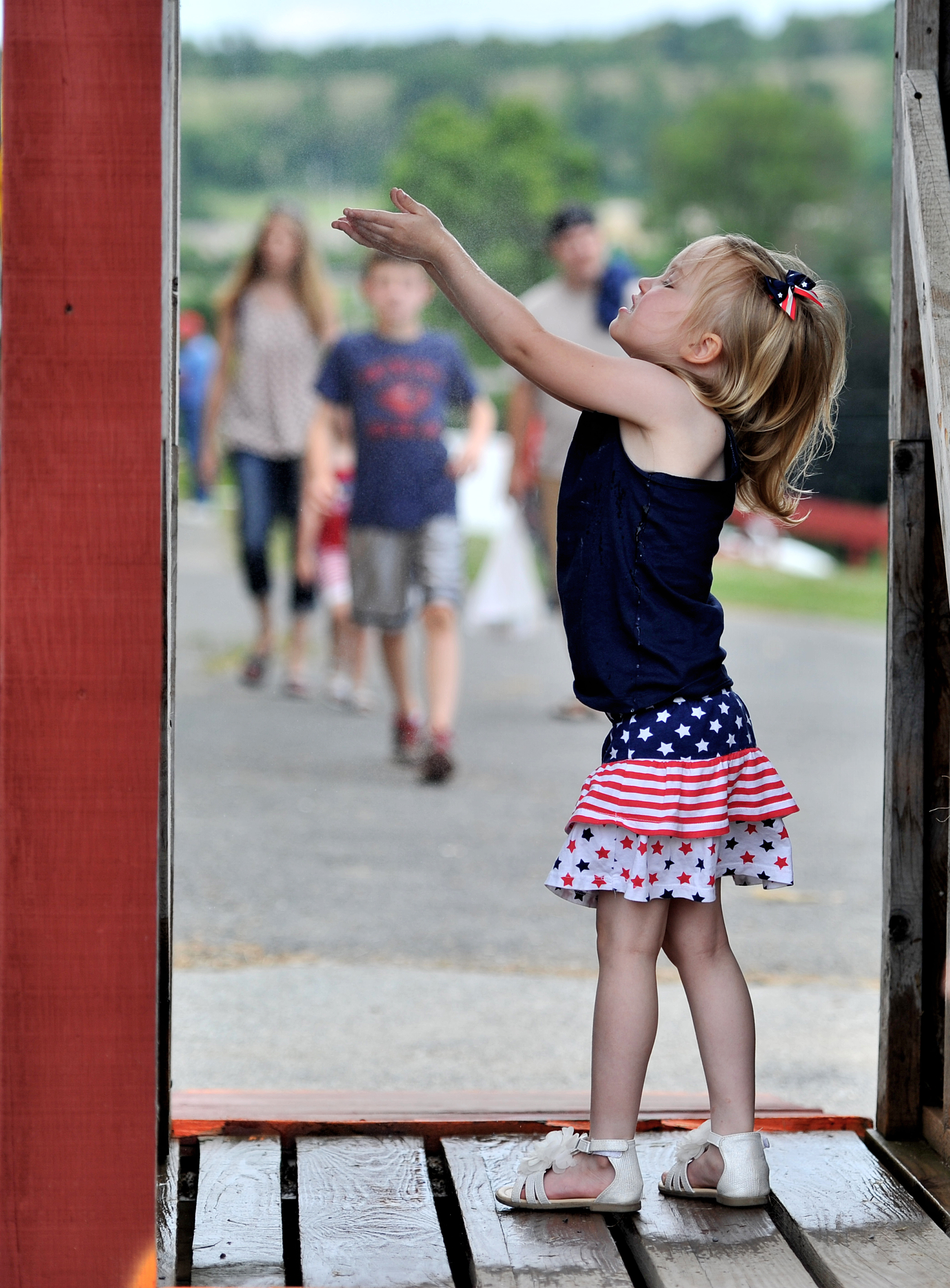 Julia Guenin, 3, of Coplay, PA, cools off under a water mist at the Kutztown Folk Festival in Kutztown, PA, on July 4, 2016. (Reading Eagle: Sarah Stier)