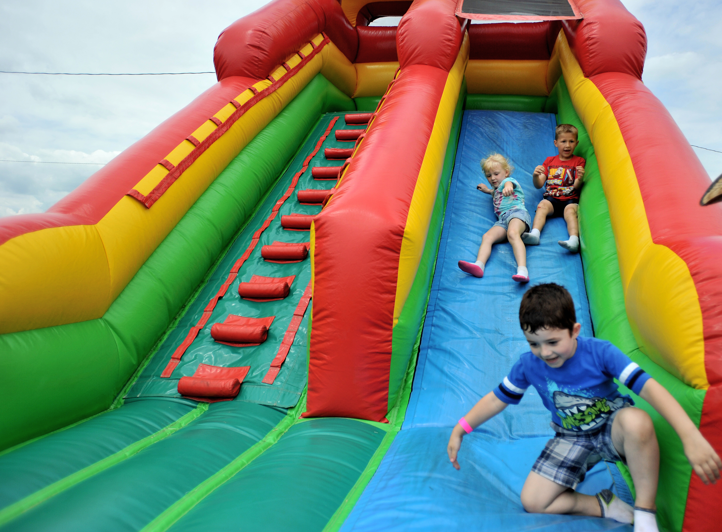 Daniel Gamble, 4, of McKeansburg, PA, slides down an inflatable slide at the Kutztown Folk Festival in Kutztown, PA, on July 4, 2016. Katie Repscher, 5, and her brother Benjamin, 7, of Bethlehem, follow closely behind. (Reading Eagle: Sarah Stier)