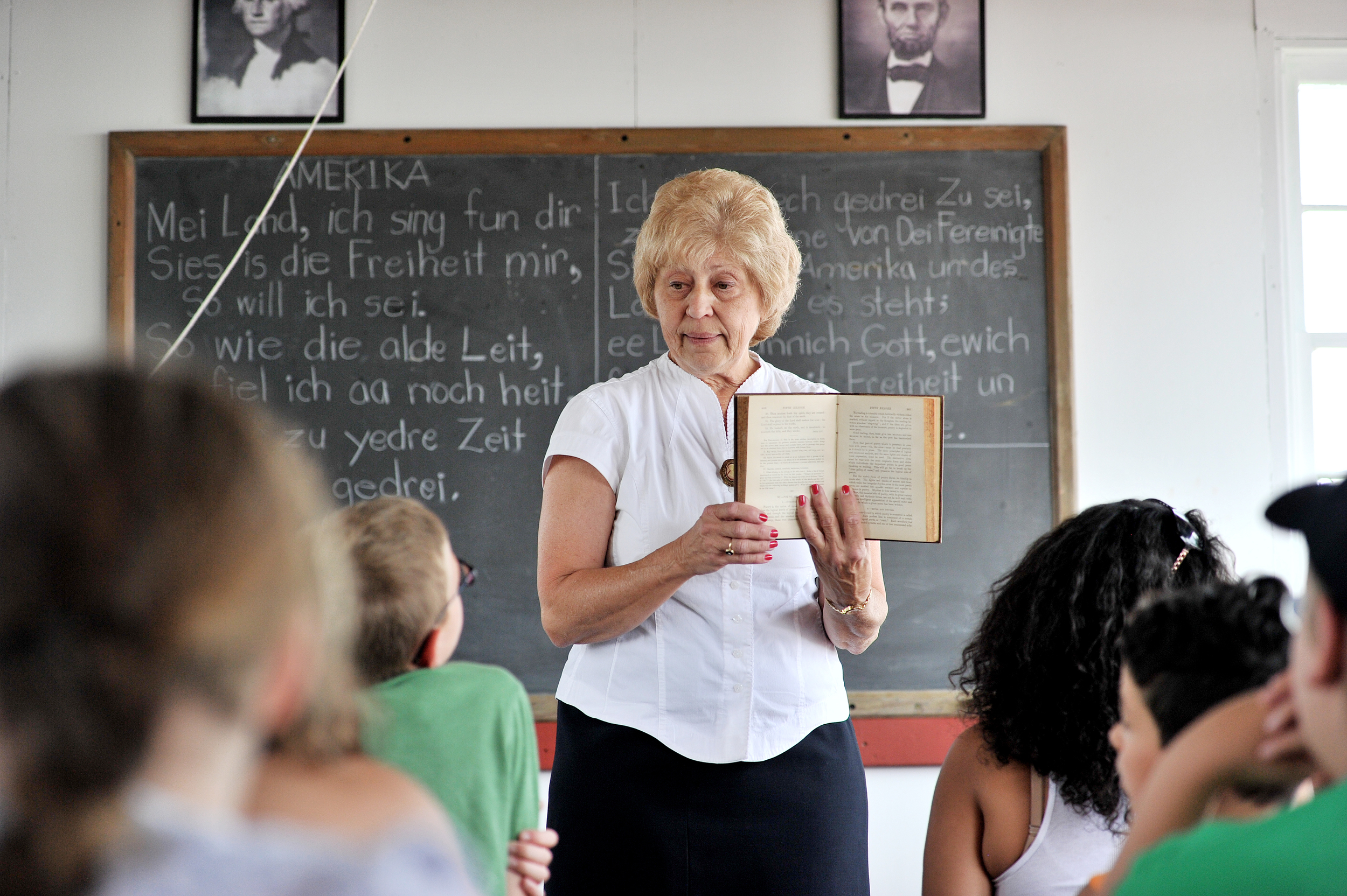 Laureen Hoffman of Kutztown demonstrates what it was like to go to school in a one-room schoolhouse at the Kutztown Folk Festival in Kutztown, PA, on July 2, 2016. (Reading Eagle: Sarah Stier)
