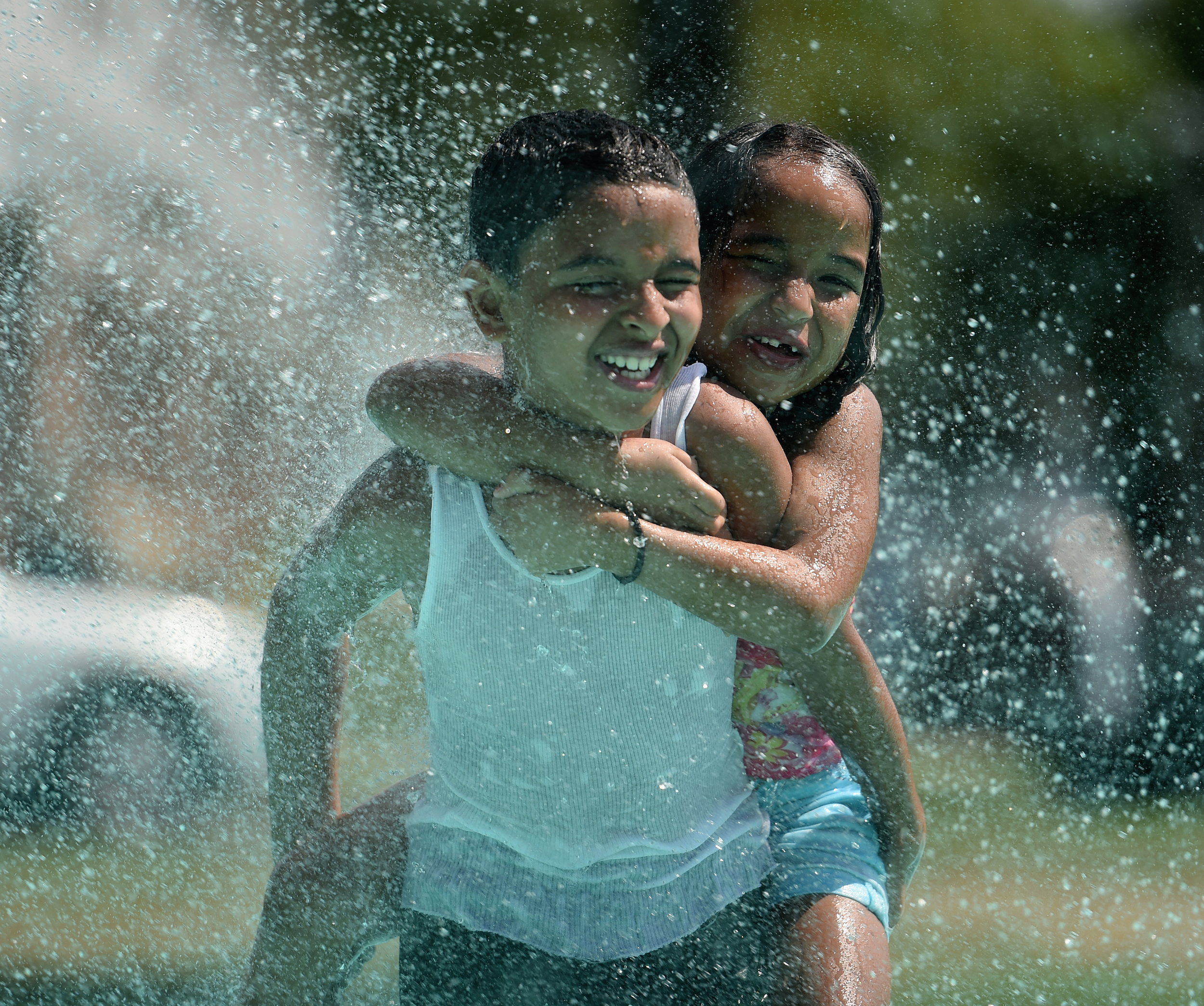 Noah Delvalle, 10, gives Leandra Tavarez, 7, of Reading a piggyback ride in the splash pad at Yarnell Park in Shillington, PA, on July 21, 2016. The temperature in Shillington that day reached 95 degrees. (Reading Eagle: Sarah Stier)