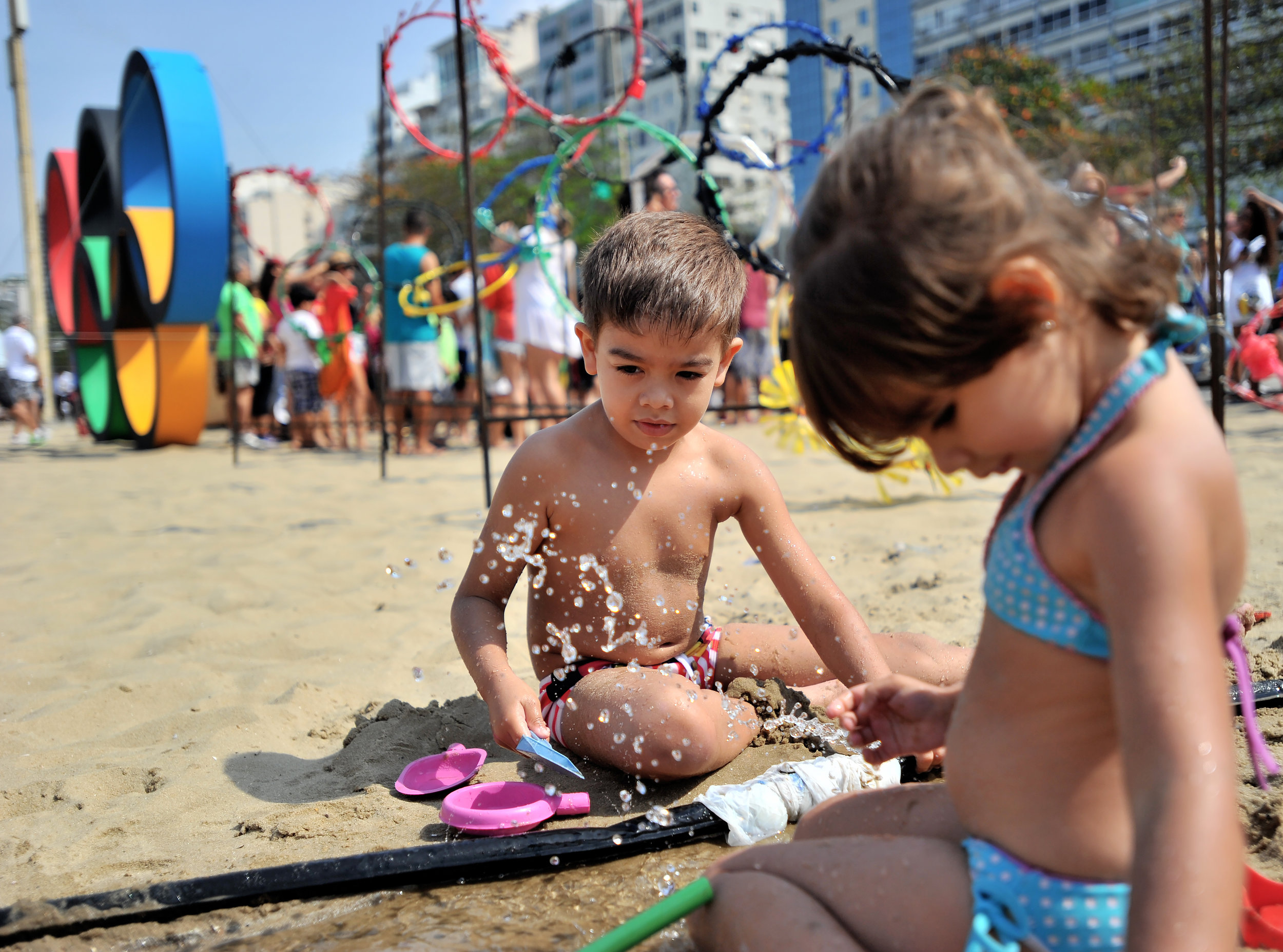 Erik Leal Temporal, 4, and his sister Melissa, 3, of Rio de Janeiro, play in the sand near the Olympic Rings at Copacabana Beach in Rio de Janeiro, Brazil, on August 7, 2016. (Sarah Stier | Ball State at the Games)