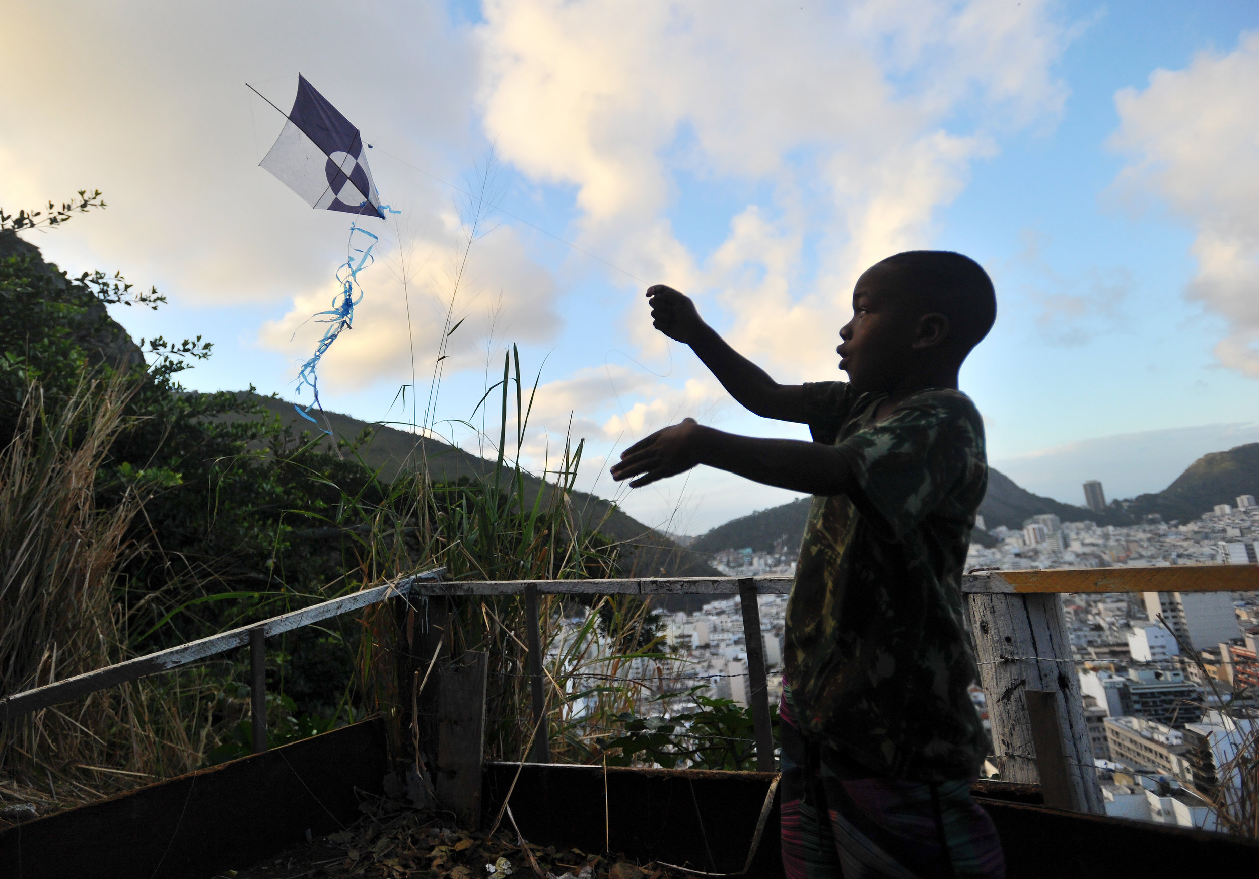 Mateus Deodoro, 7, flies a kite in the favela that he lives in in Rio de Janeiro, Brazil, on August 12, 2016. The children build their own kites and attempt to catch their friends' kites in order to win the game. (Sarah Stier | Ball State at the Games)