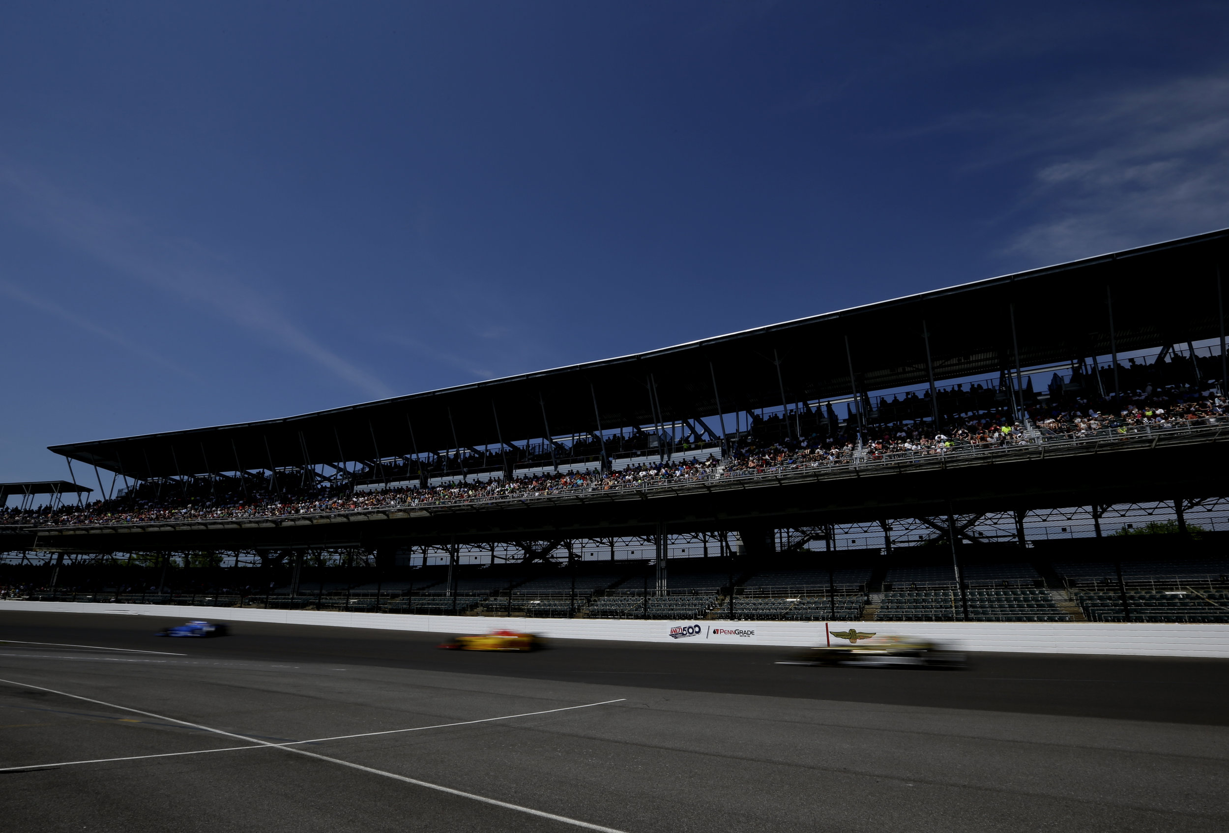 Cars fly by on the track during the practice race on Carb Day for the 101st running of the Indianapolis 500 at Indianapolis Motor Speedway on Friday, May 26, 2017.