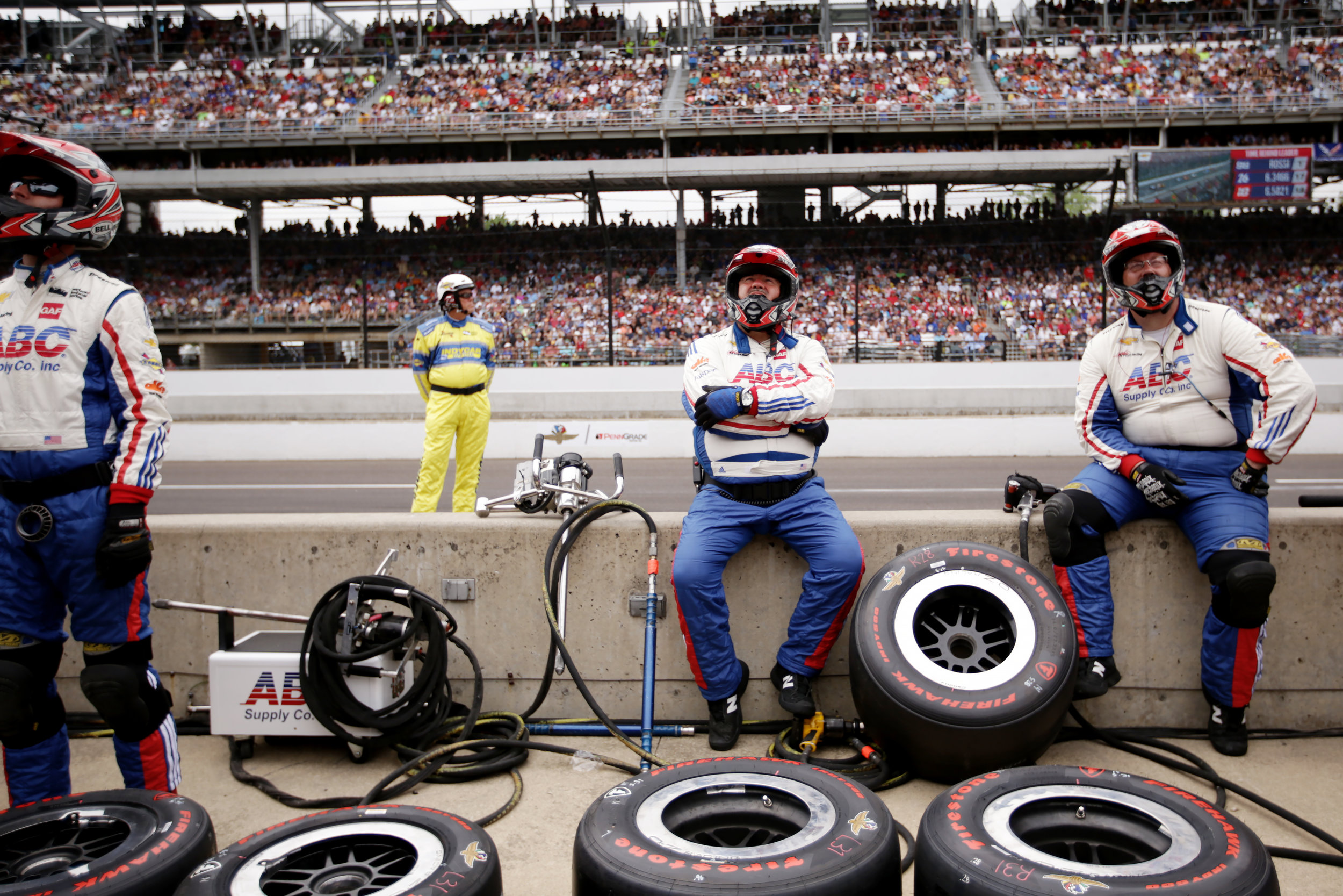 An IndyCar driver's pit crew watches the big screen as the cars move through Turns 2, 3, and 4.