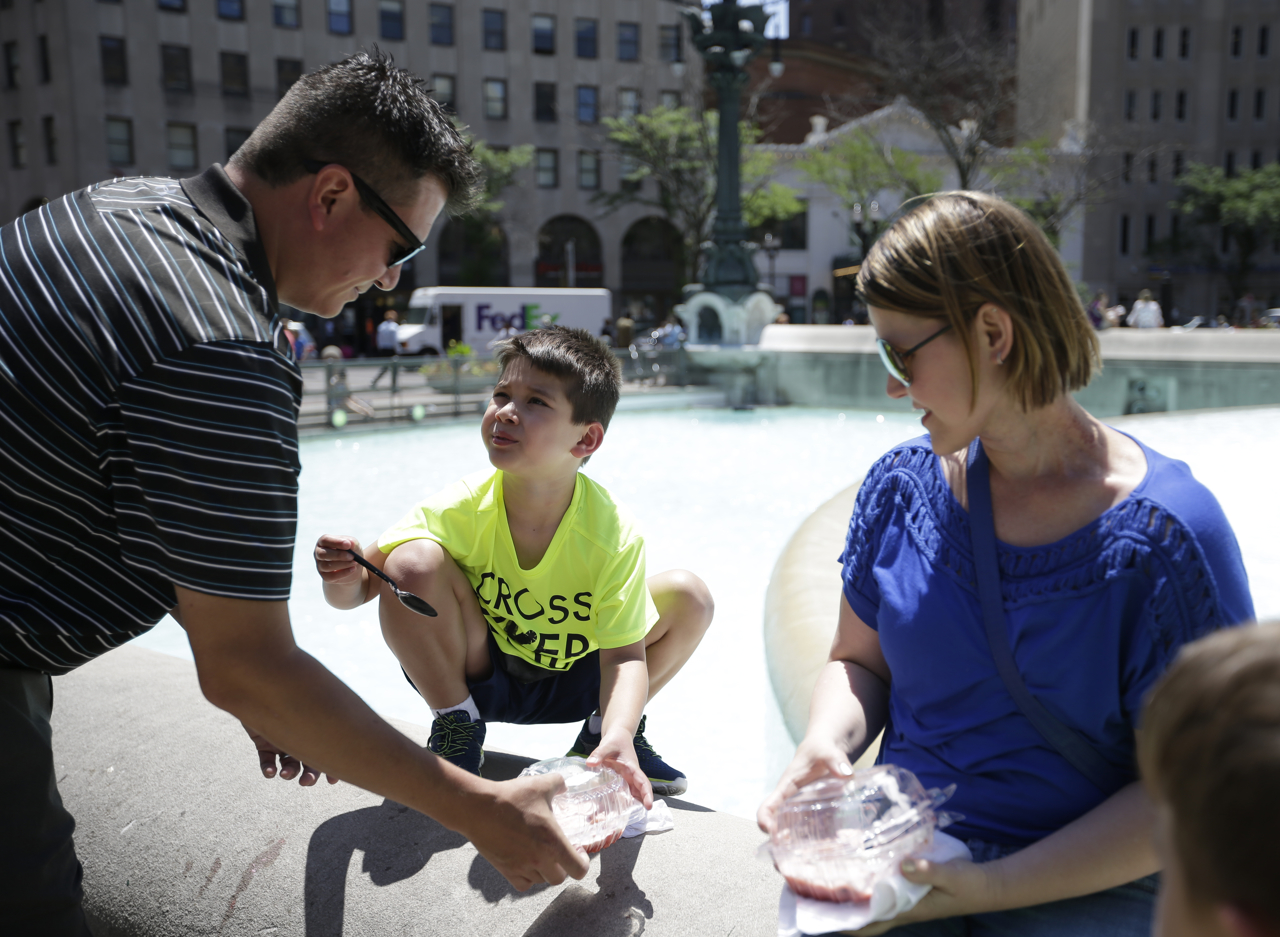 Jeff Moffatt hands his son, Devin, 8, a container of strawberry shortcake to enjoy with his mother, Belinda, at the 52nd Annual Strawberry Festival at Monument Circle in downtown Indianapolis on Thursday, June 8, 2017.