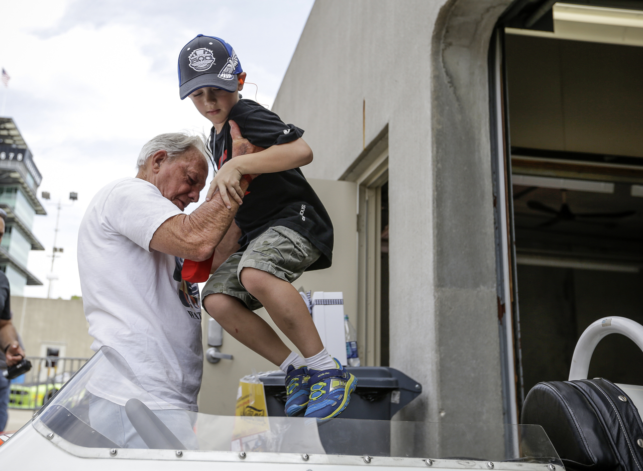 Bud Taylor hoists Andrew Lewis, 7, into his car in at the SVRA Brickyard Vintage Race at Indianapolis Motor Speedway on Saturday, June 17, 2017.