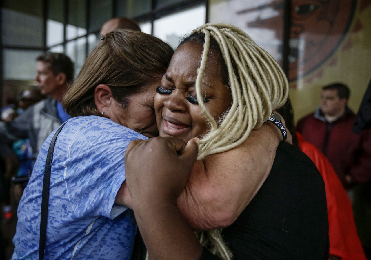 """Peggy Meyer (left) consoles Ashley Thomas (right) at the Justice for Aaron Bailey rally at City Market on Friday, June 30, 2017. """"If I don't do something about this injustice now, how will I better my sons' futures?"""" says Thomas."""
