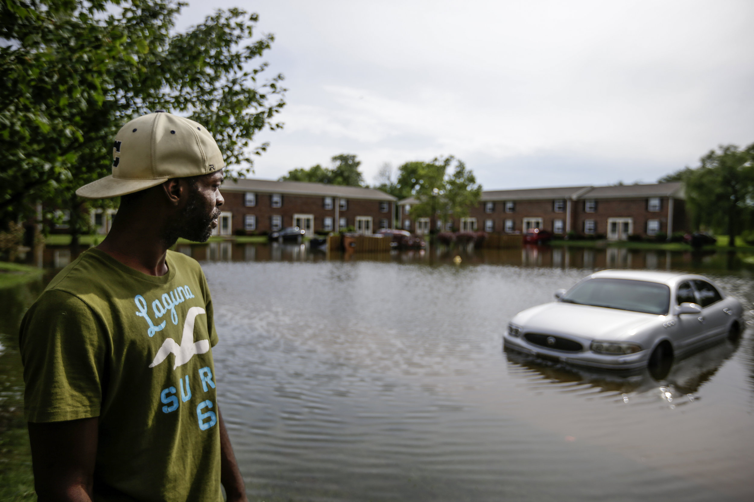 """Nials Johnson looks at his submerged Buick Sabre in Franklin, Ind., on Tuesday, July 11, 2017. Johnson's car had been stolen the previous week, and he had only had it back for three days before the floods hit. """"It's my baby,"""" says Johnson."""