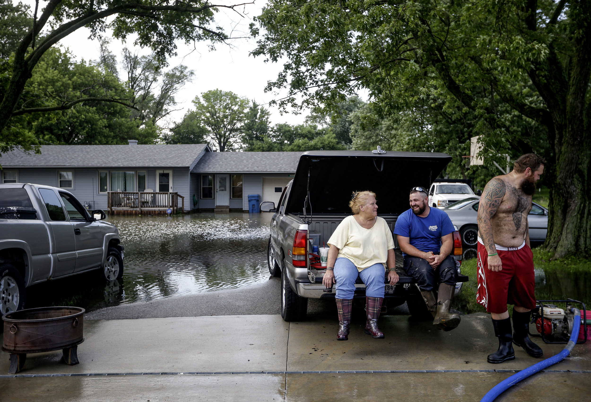Margaret Morgan, Joe Forbes, and Kyle Morgan wait for a case of beer to arrive while a pump drains the water from Kyle Morgan's front yard in Whiteland, Ind., on Tuesday, July 11, 2017.