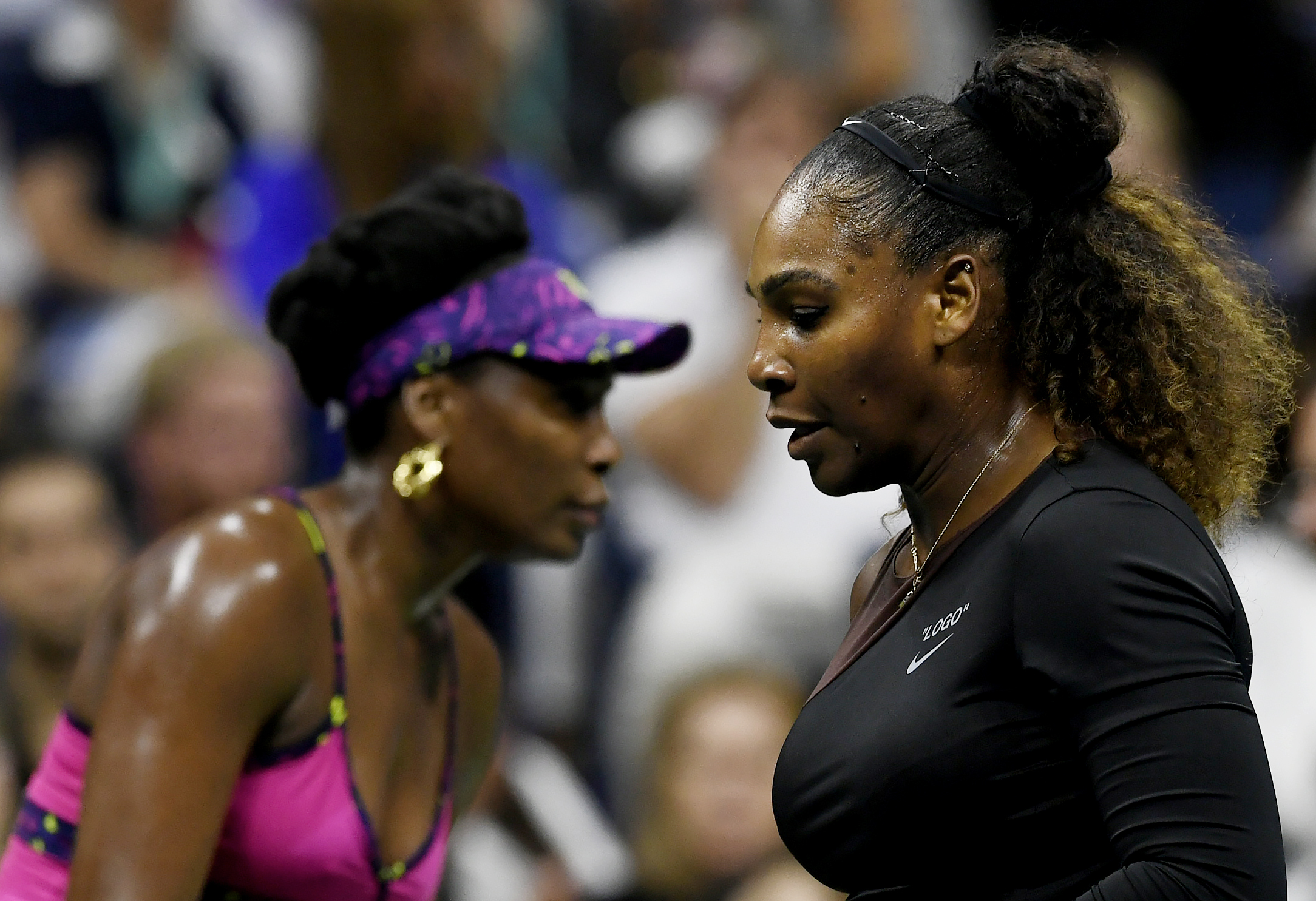Venus Williams (L) and Serena Williams of the United States change ends during their women's singles third round match on Day Five of the 2018 US Open at the USTA Billie Jean King National Tennis Center on August 31, 2018 in the Flushing neighborhood of the Queens borough of New York City.