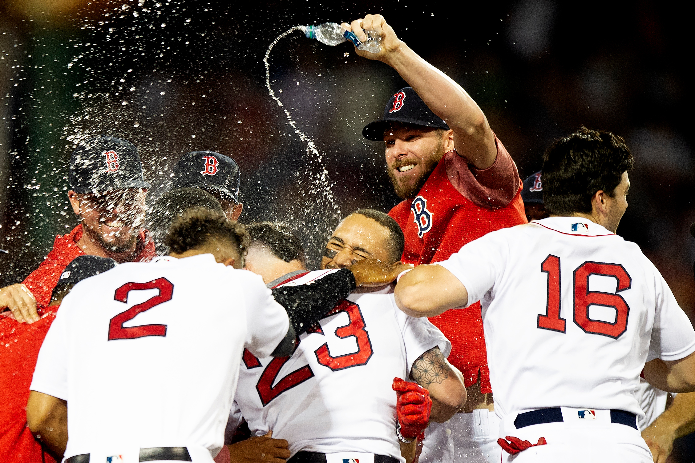 The Boston Red Sox swarm catcher Blake Swihart after he made a hit that ended the thirteen-inning game against the Philadelphia Phillies at Fenway Park in Boston, Massachusetts on Monday, July 30, 2018.