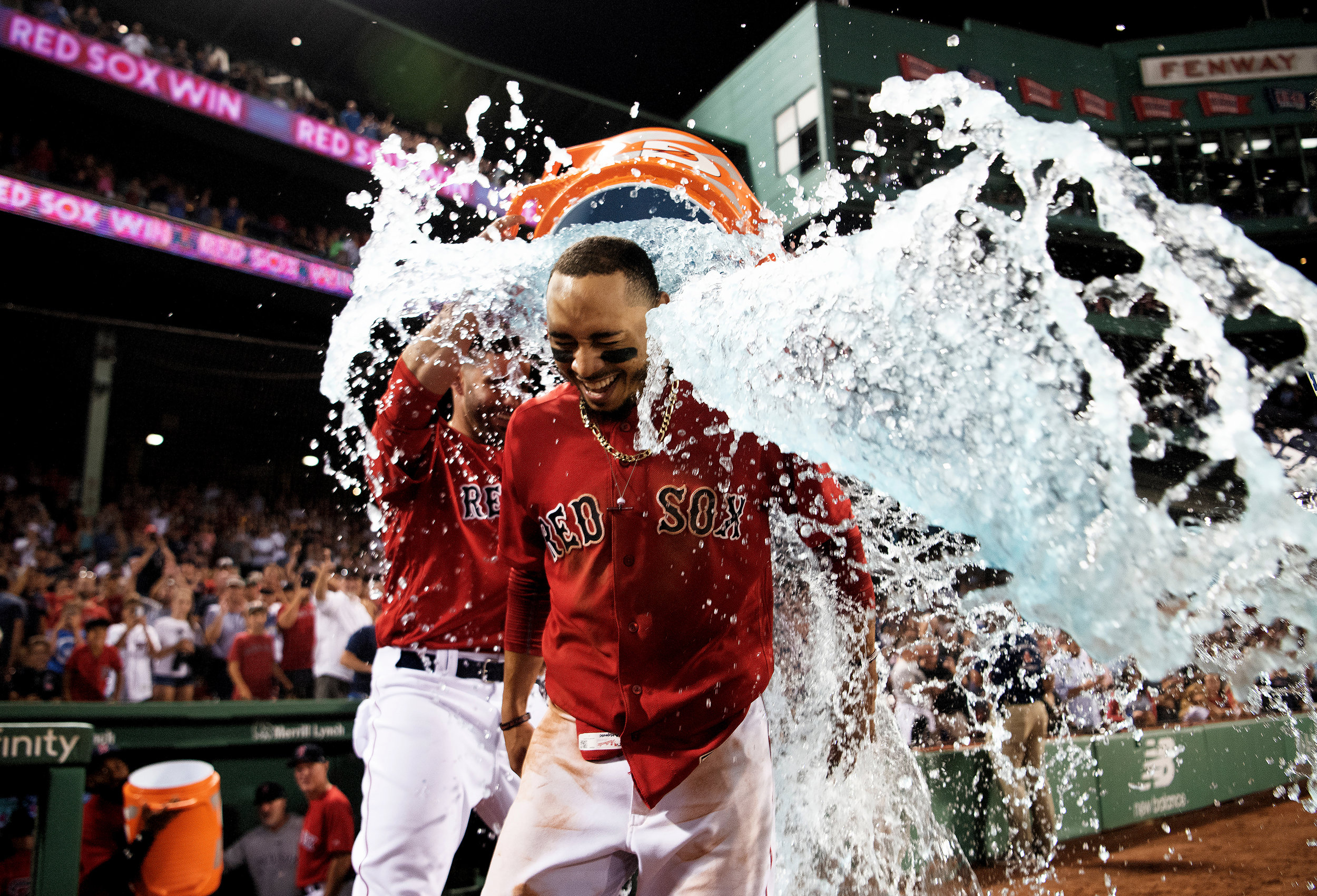 Boston Red Sox outfielder Mookie Betts receives a Gatorade shower after hitting a home run to end the game in the 10th inning during the game against the Minnesota Twins at Fenway Park in Boston, Massachusetts on Friday, July 27, 2018.