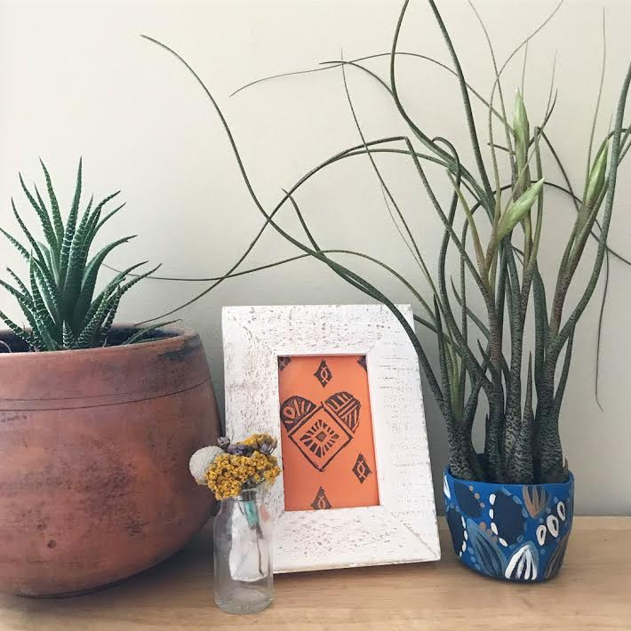 Planters look beautiful next to frames. You can also showcase stamped prints in mini frames.