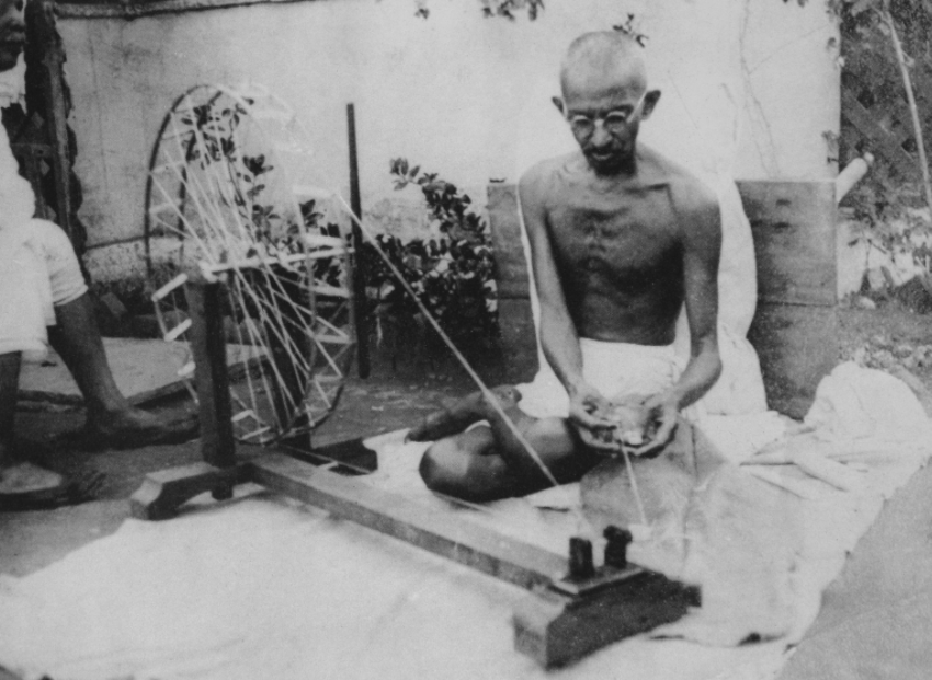 Ghandi spinning on his Charkha. Photo wikimedia commons.