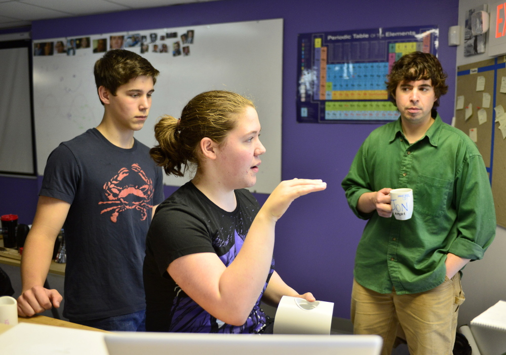 Baxter Academy student Erin Whitney talks about her team's engineering project as student Caedan Holdan, left, and engineering teacher Jonathan Amory listen