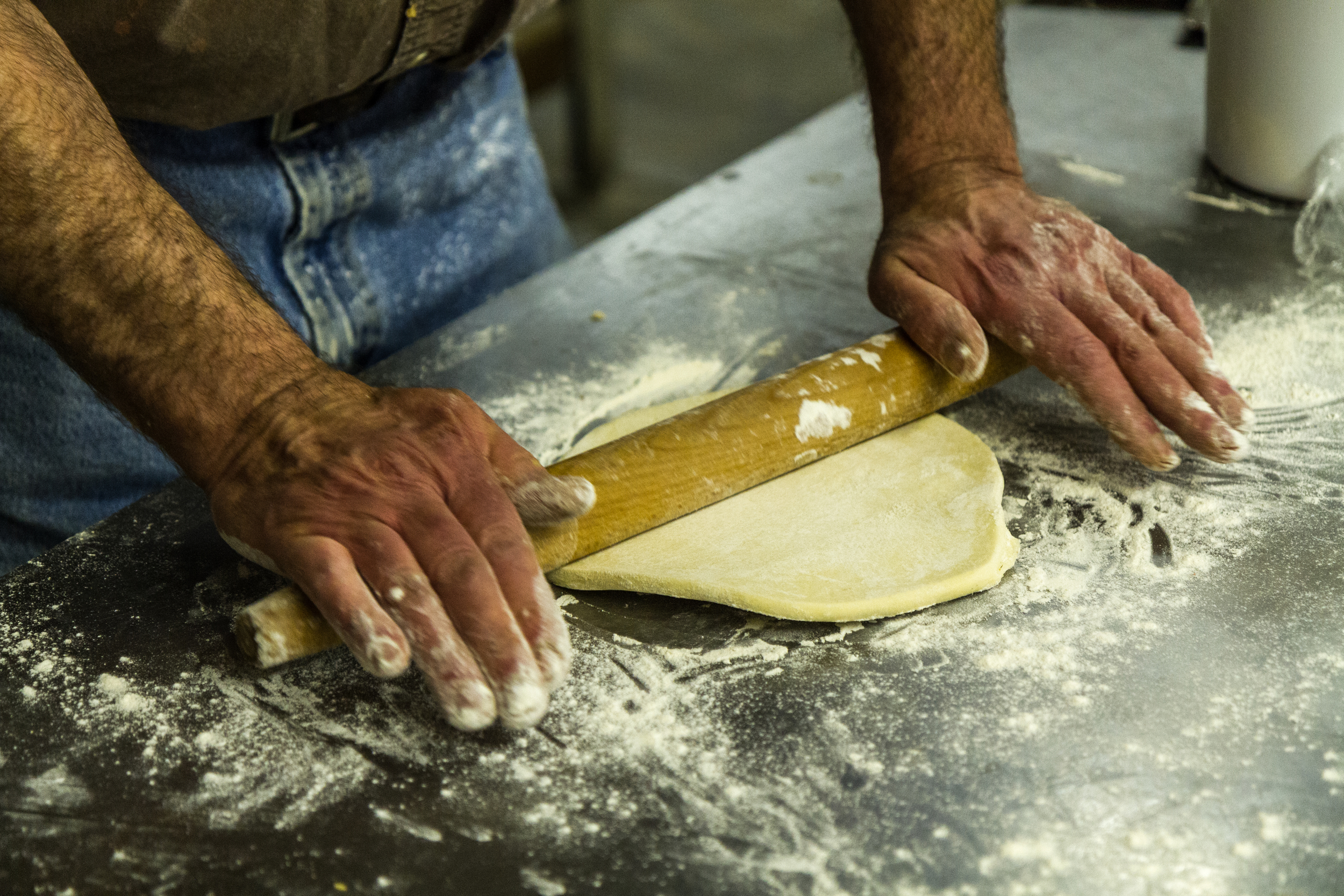 Ken's hands roll out dough, using a sustainably harvested reclaimed rolling pin. Really.