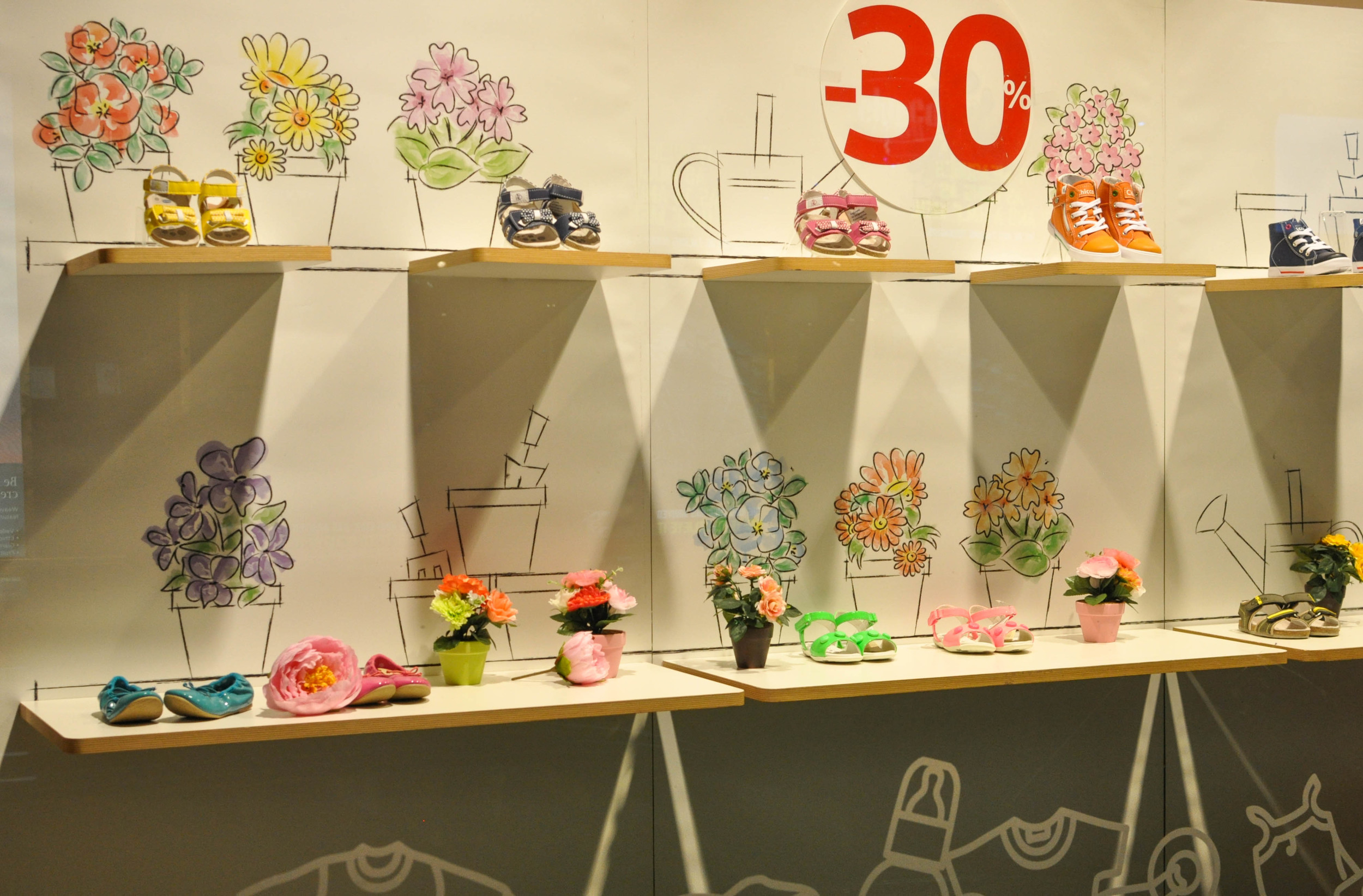 CHICCO    Chicco's summer shoe display was supported by simple yet cute hand-drawn art depicting a spring/summer garden scene. The material used was thick butchers-type paper in panels. Coloured pots of fake flowers also enlivened the scene.