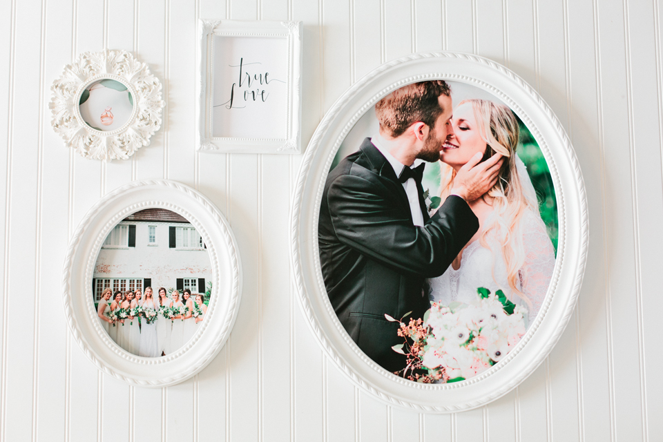 """Picture of a wall gallery of wedding images.  Each picture is in a white frame.  Wedding rings are in one picture.  A bride and bridesmaids are in another picture.  A bride and groom are in the third picture.  The fourth is hand lettering in a white frame that says, """"true love"""".  This gallery showcases the work of Debra Eby, Jacksonville fine art wedding photographer."""