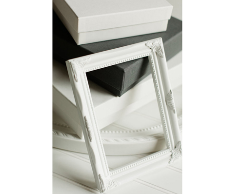 Image of photograph album boxes that are white and grey, stacked.  Two white empty frames are also in the picture.  This shows the viewer brand packaging of Debra Eby, Jacksonville Fine Art Wedding Photography.  This image also tells the importance of investing in good photography.