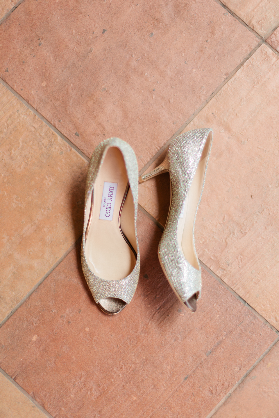 Picture of Jimmy Choo bridal heels laying on terracotta tile flooring.  This is at the TPC Sawgrass in Ponte Vedra, Florida