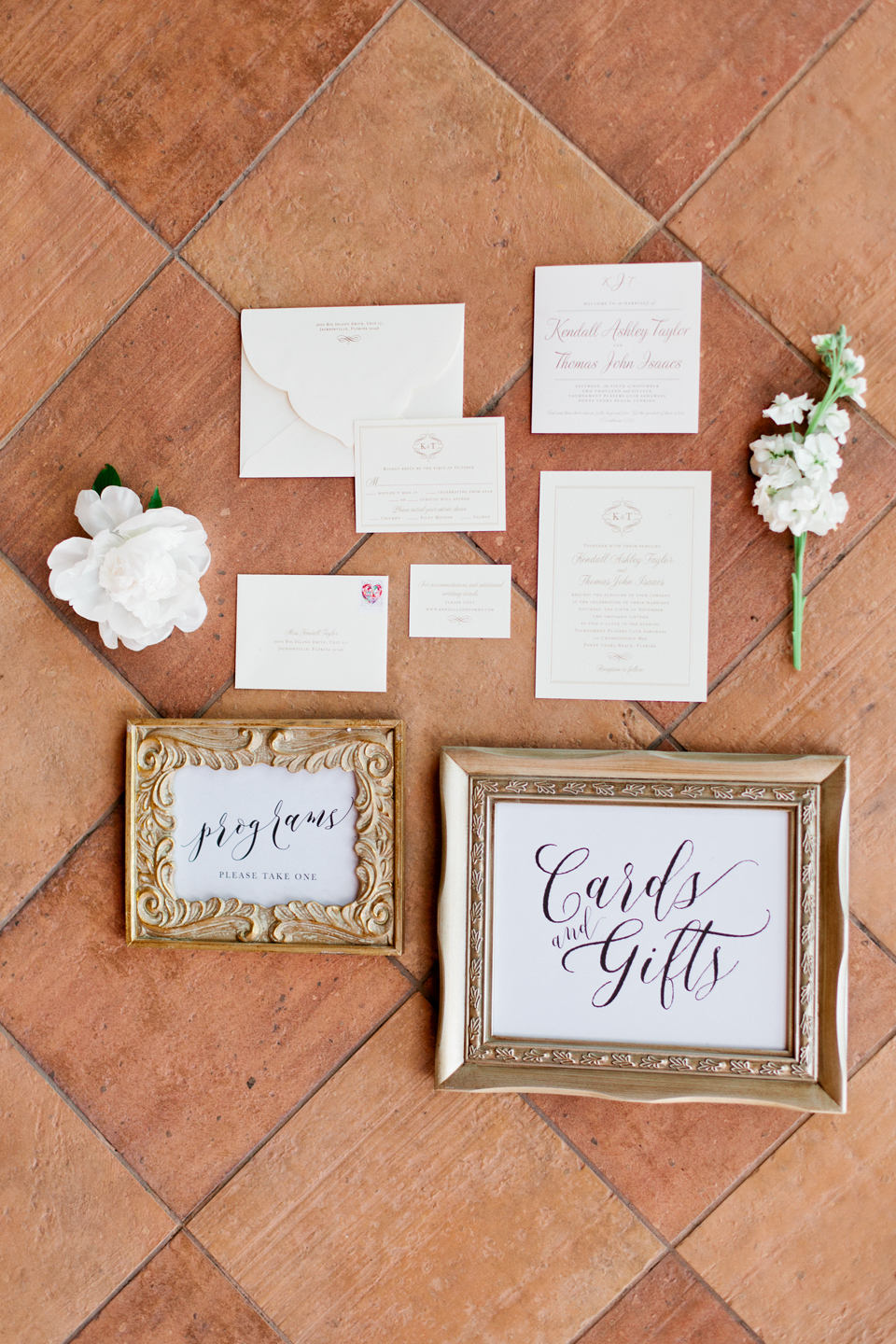 Picture of a wedding stationary suite with hand lettered signage and floral accents.  These are laying on terracotta tile flooring at the TPC Sawgrass in Ponte Vedra, Florida
