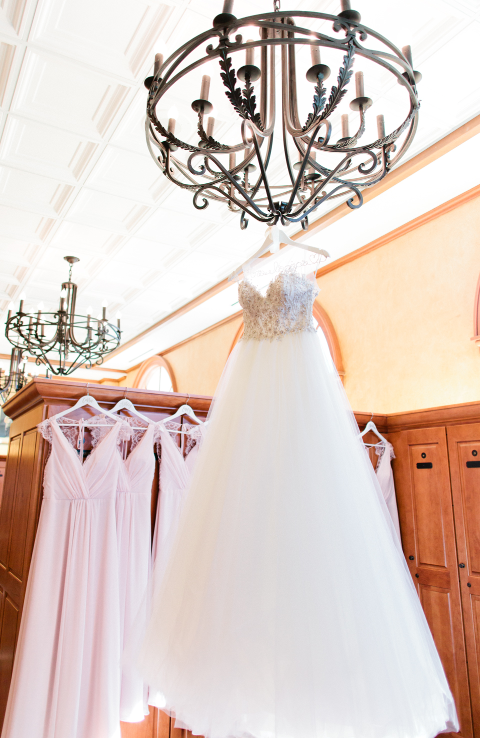 Image of a Calvet Couture bridal gown hanging on a chandelier with bridesmaid gowns in the background.  This is a wedding at TPC Sawgrass in Ponte Vedra, Florida