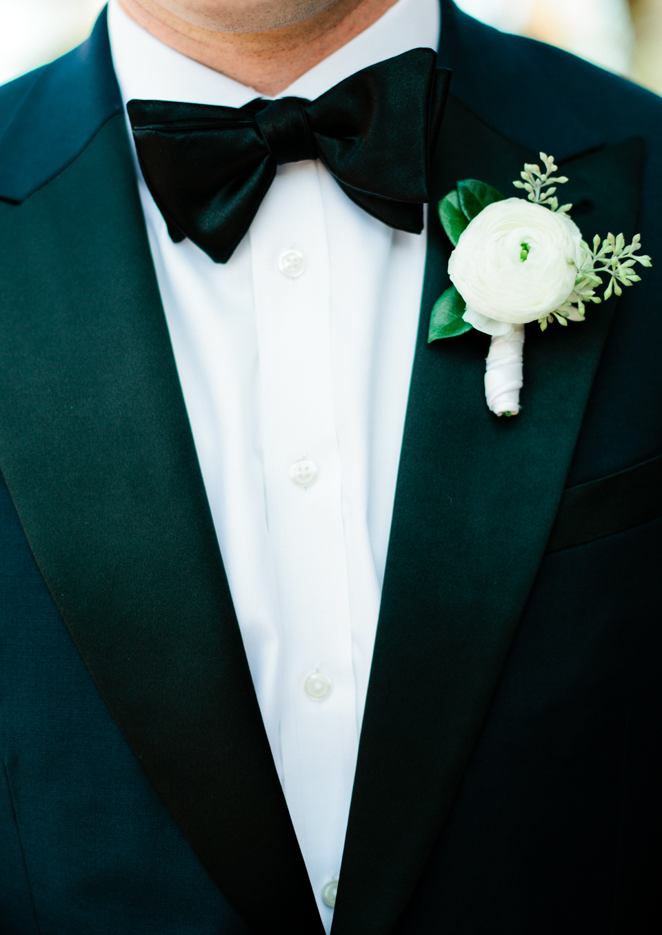 Picture of a groom wearing a black tuxedo with a white flower boutonniere at the TPC Sawgrass in Ponte Vedra, Florida